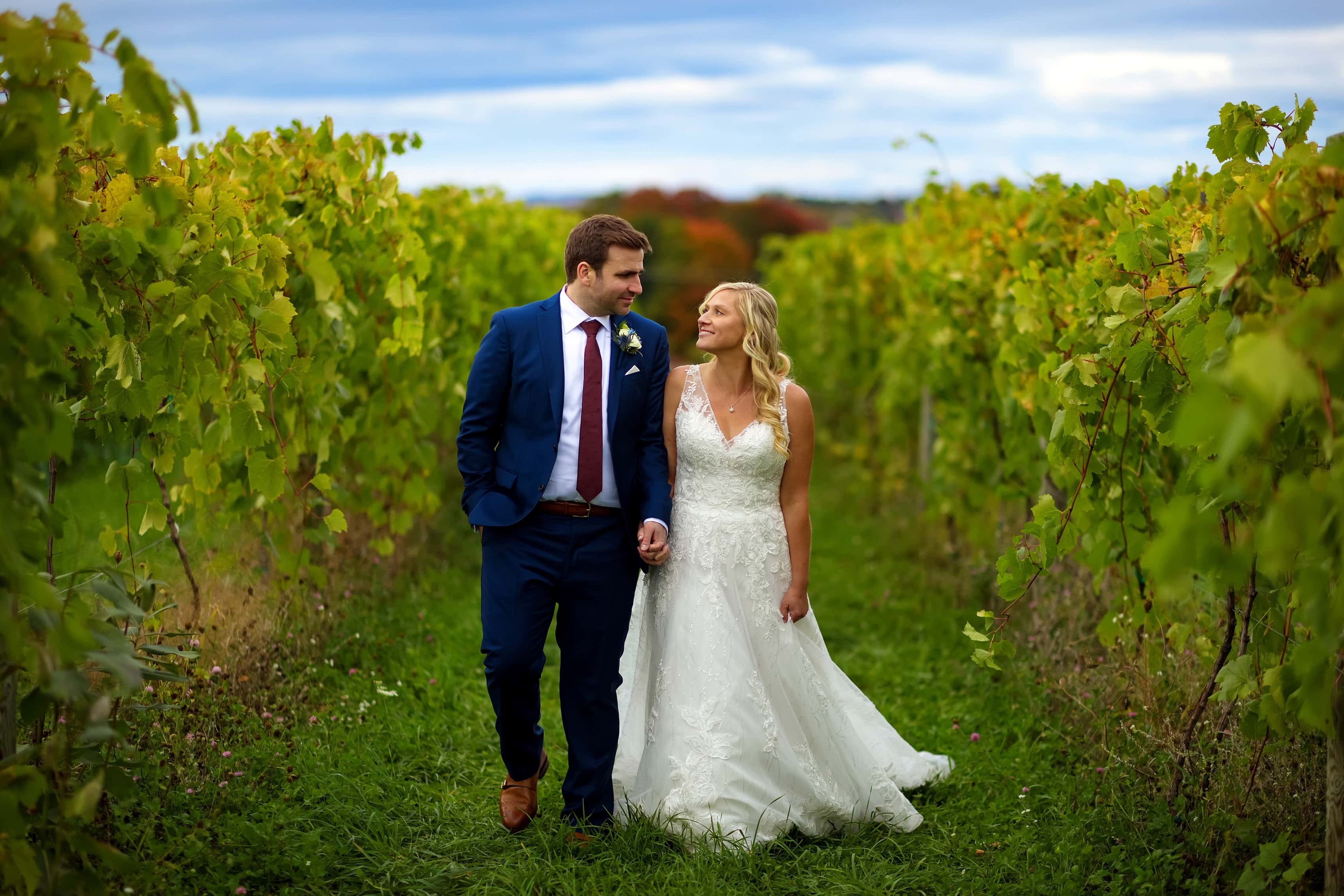 bride and groom walk through vineyard for wedding portraits at Petoskey Farms Vineyard & Winery with fall colors in the background