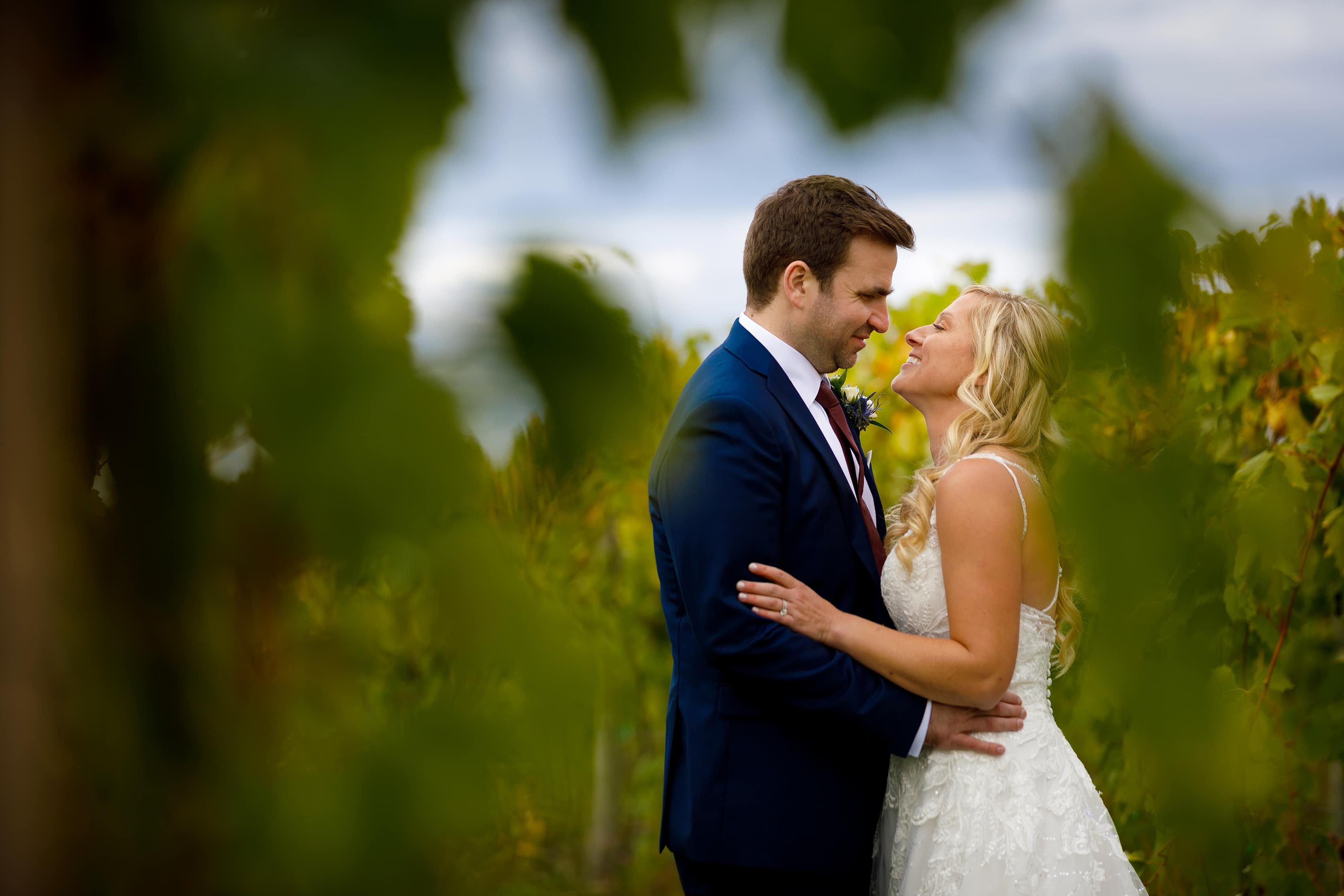 bride and groom pose in vineyard for wedding portraits at Petoskey Farms Vineyard & Winery with fall colors in the background