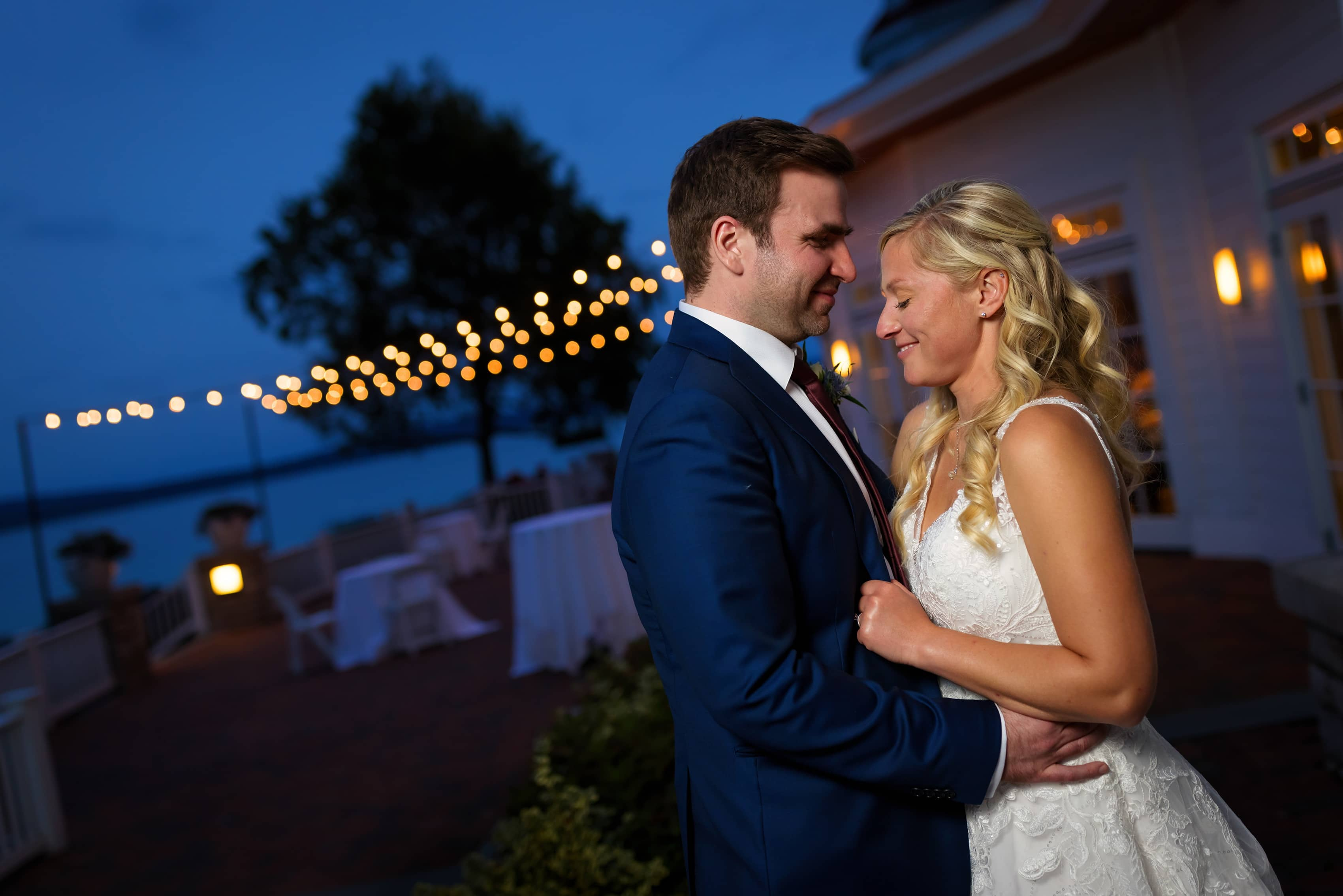 bride and groom pose for wedding portraits with twilight sky and market lights in the background at Bay Harbor Inn in Petoskey, Michigan