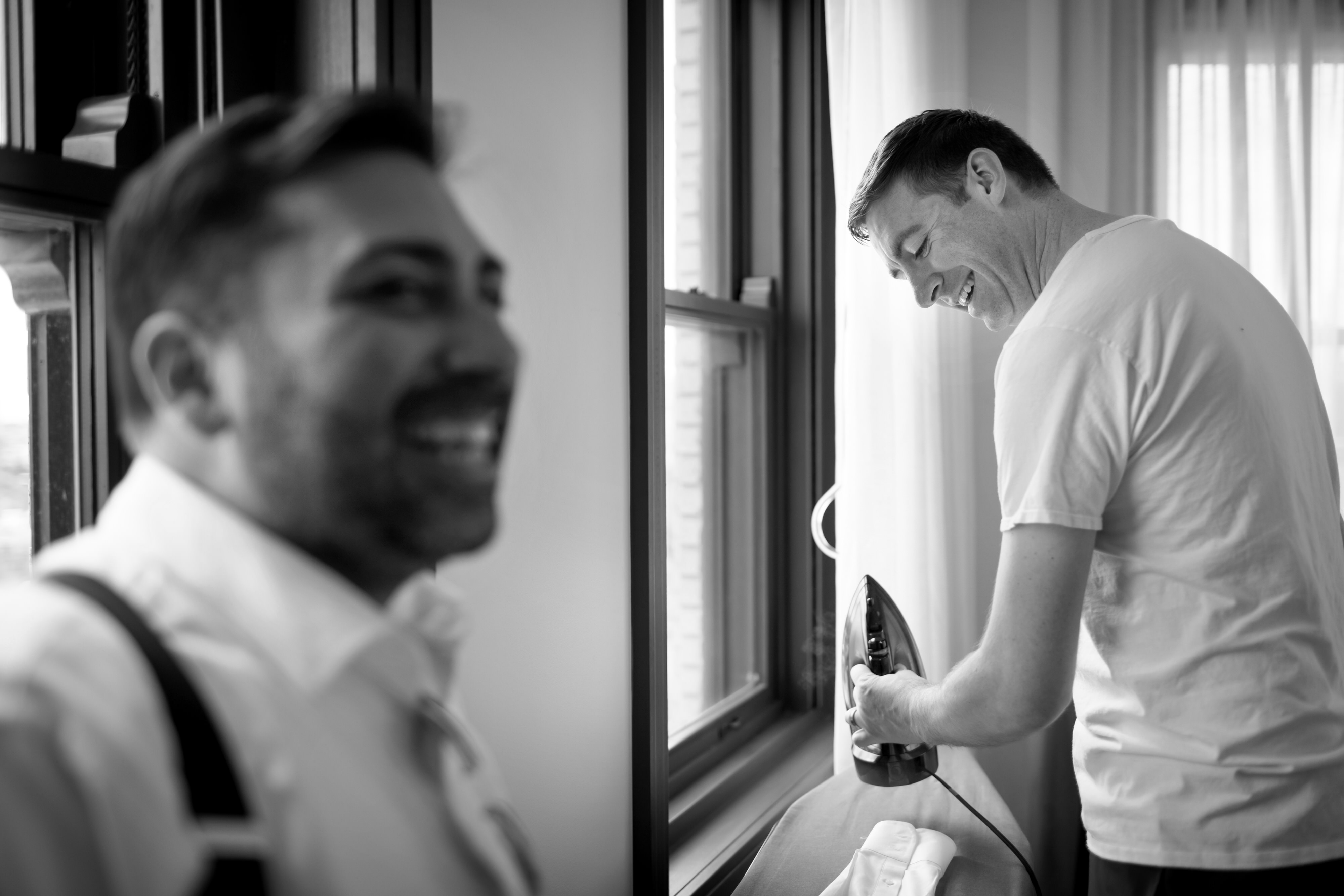 Groom laughs while getting ready for a wedding at the Robey Hotel
