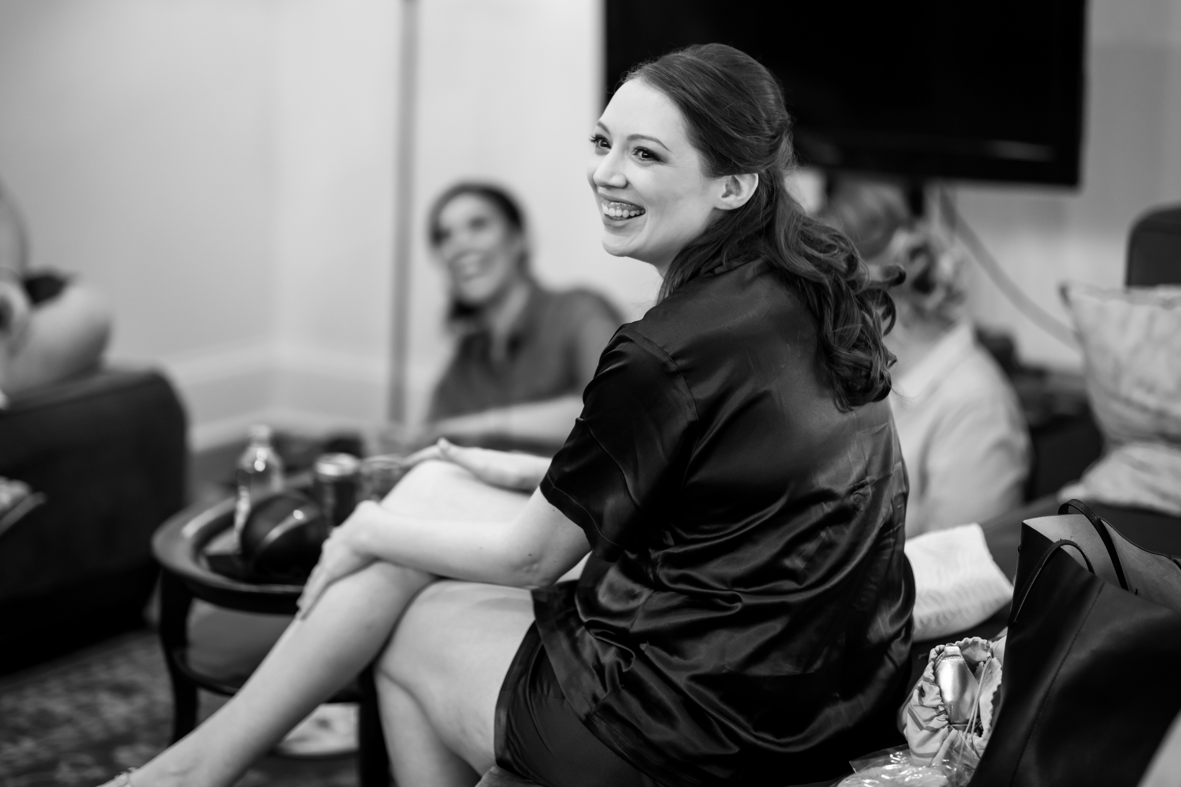 bridesmaids laugh while getting ready for a wedding