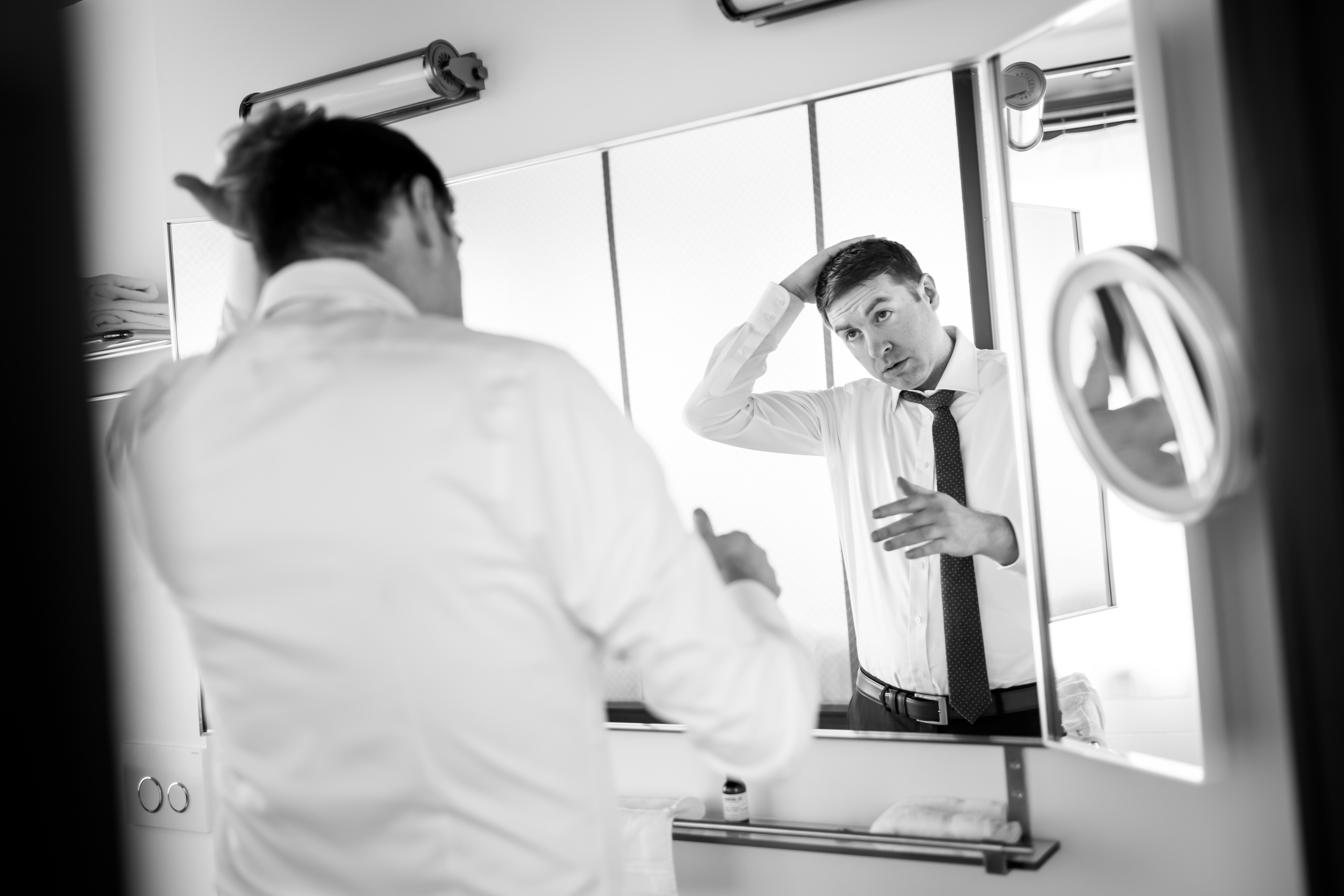 Groom does his tie while getting ready for a wedding at the Robey Hotel