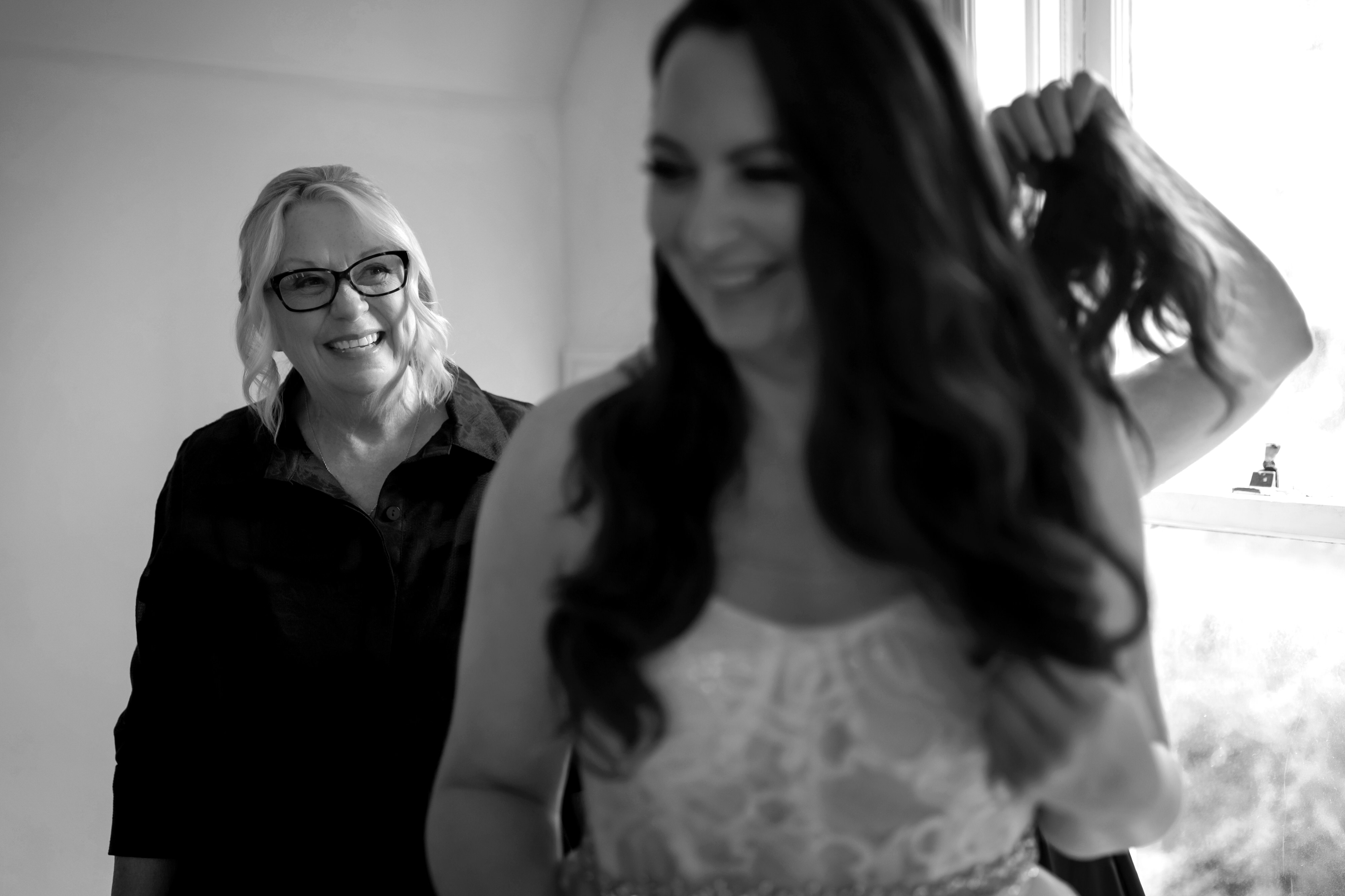 mom smiles at daughter in wedding dress