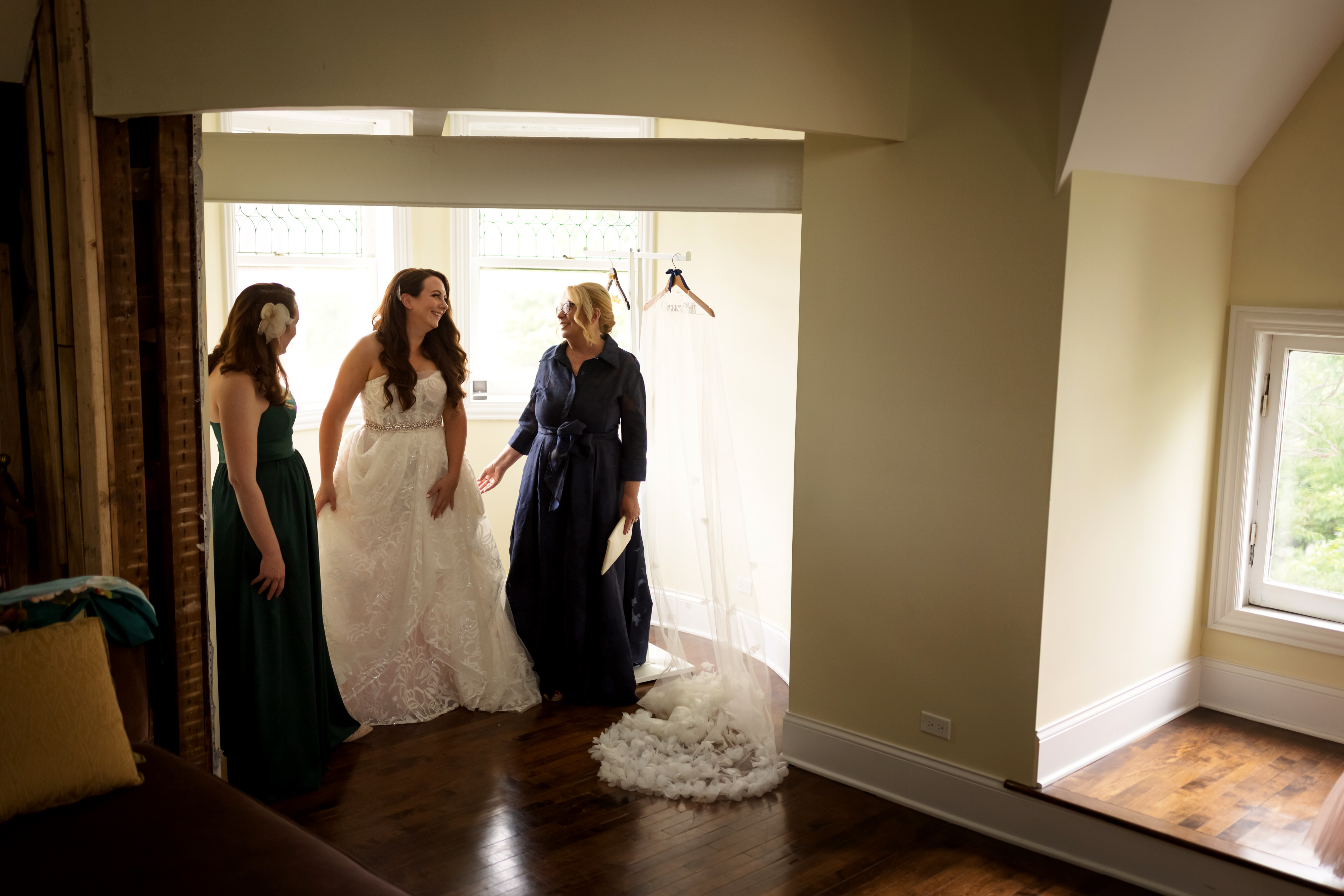 mom and sister help bride get ready in her wedding dress