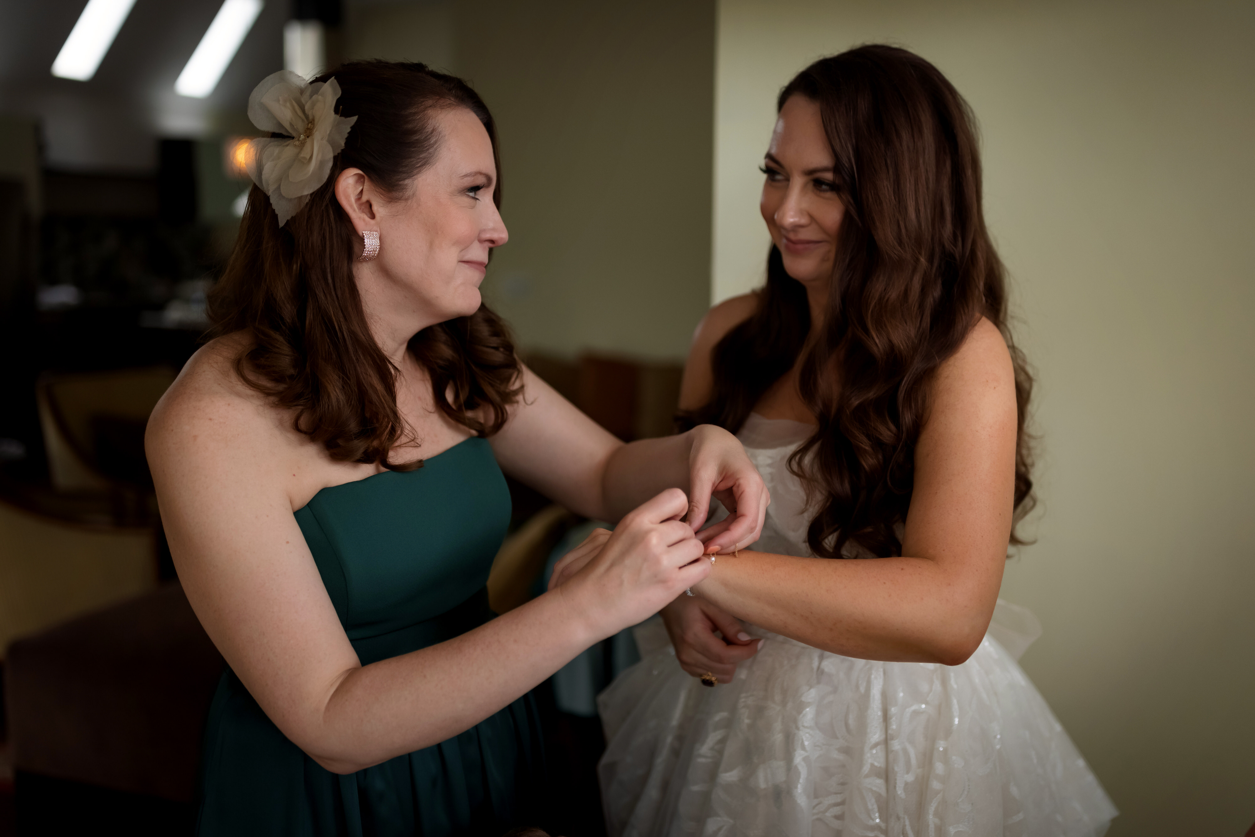 sister helps bride put on jewelry while getting ready for wedding