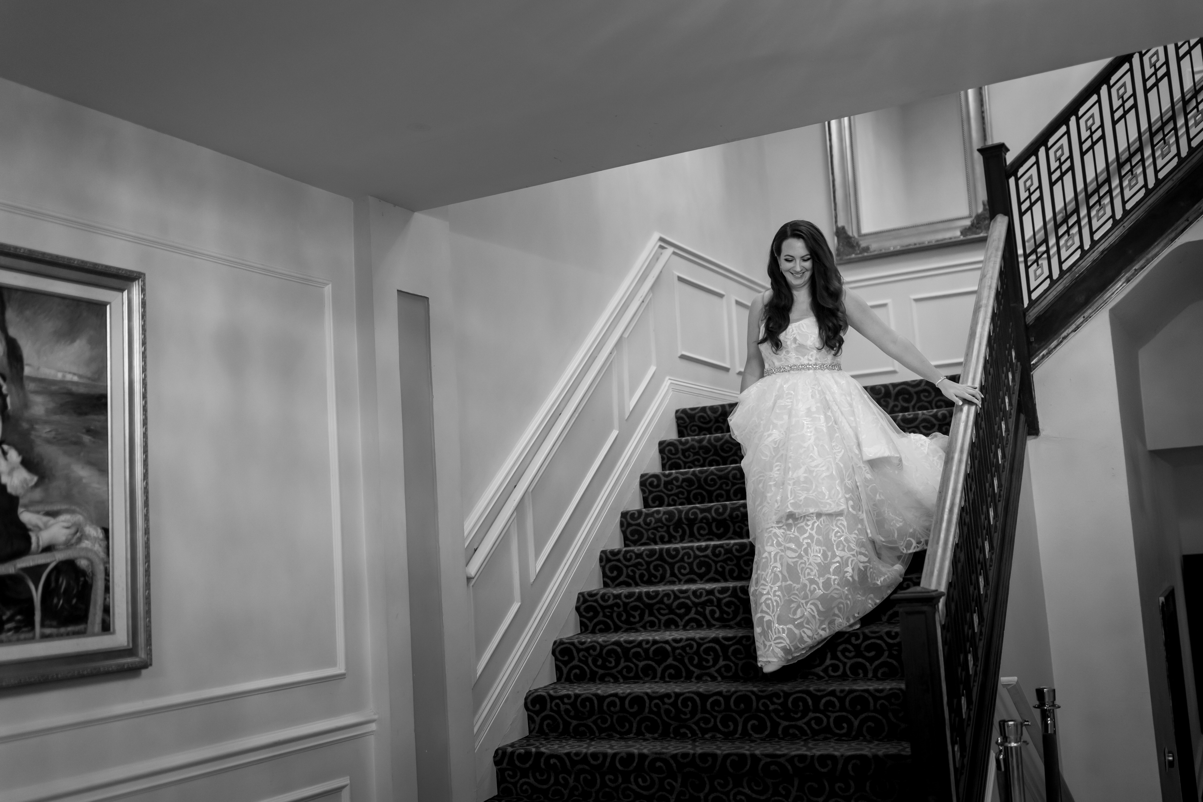 black and white photo of bride walking down stairs at Stan Mansion in Chicago