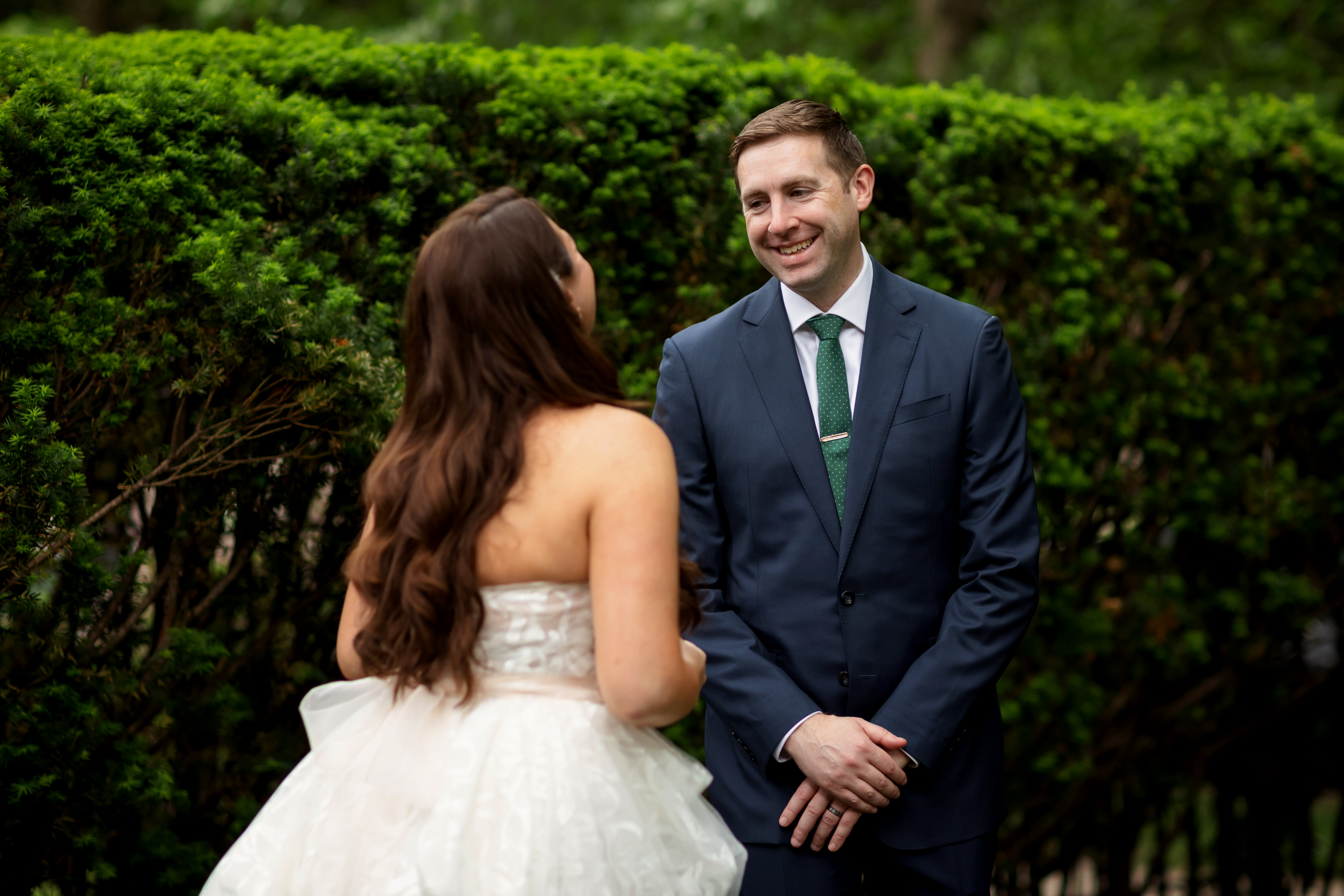 first look between bride and groom with green bushes in background