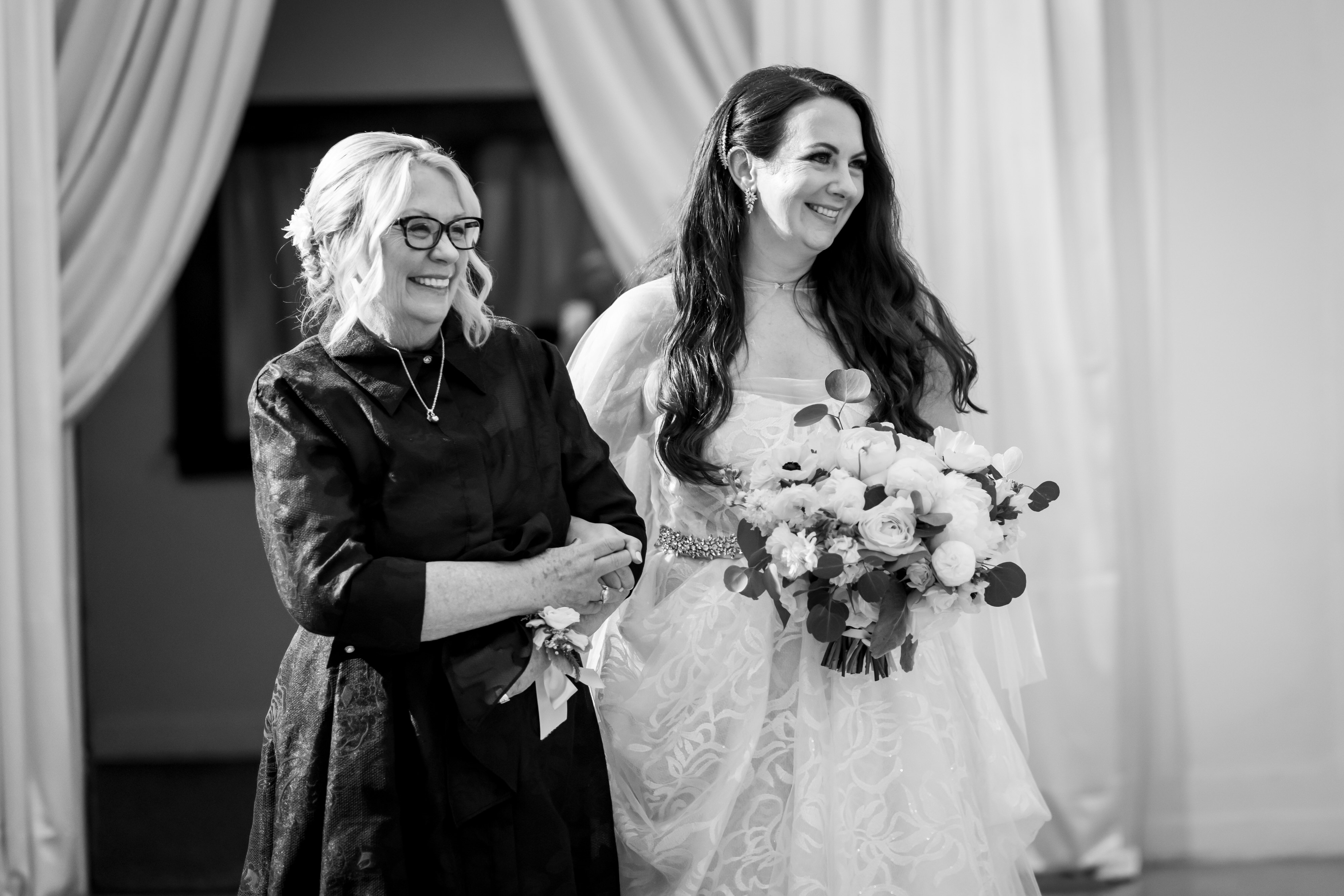 bride and mother walk down the aisle