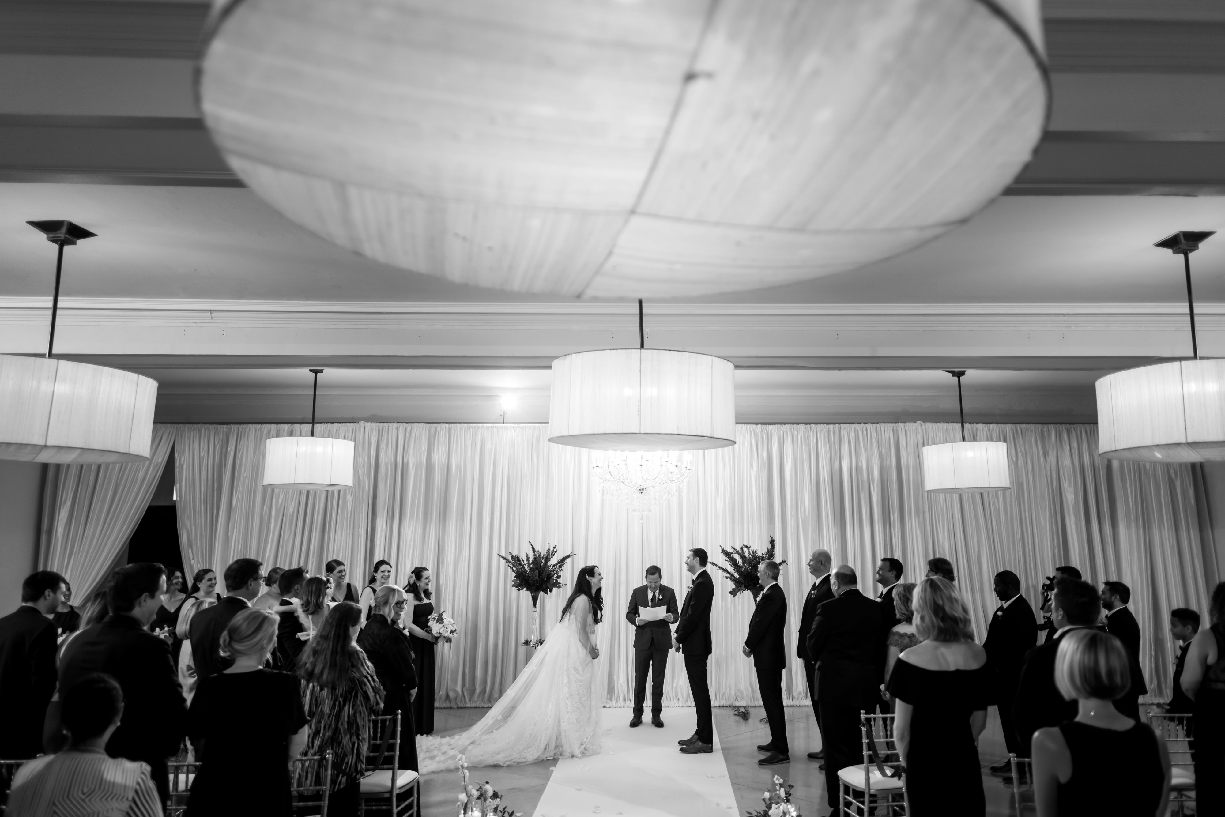 black and white photo of wedding ceremony on lower level at Stan Mansion