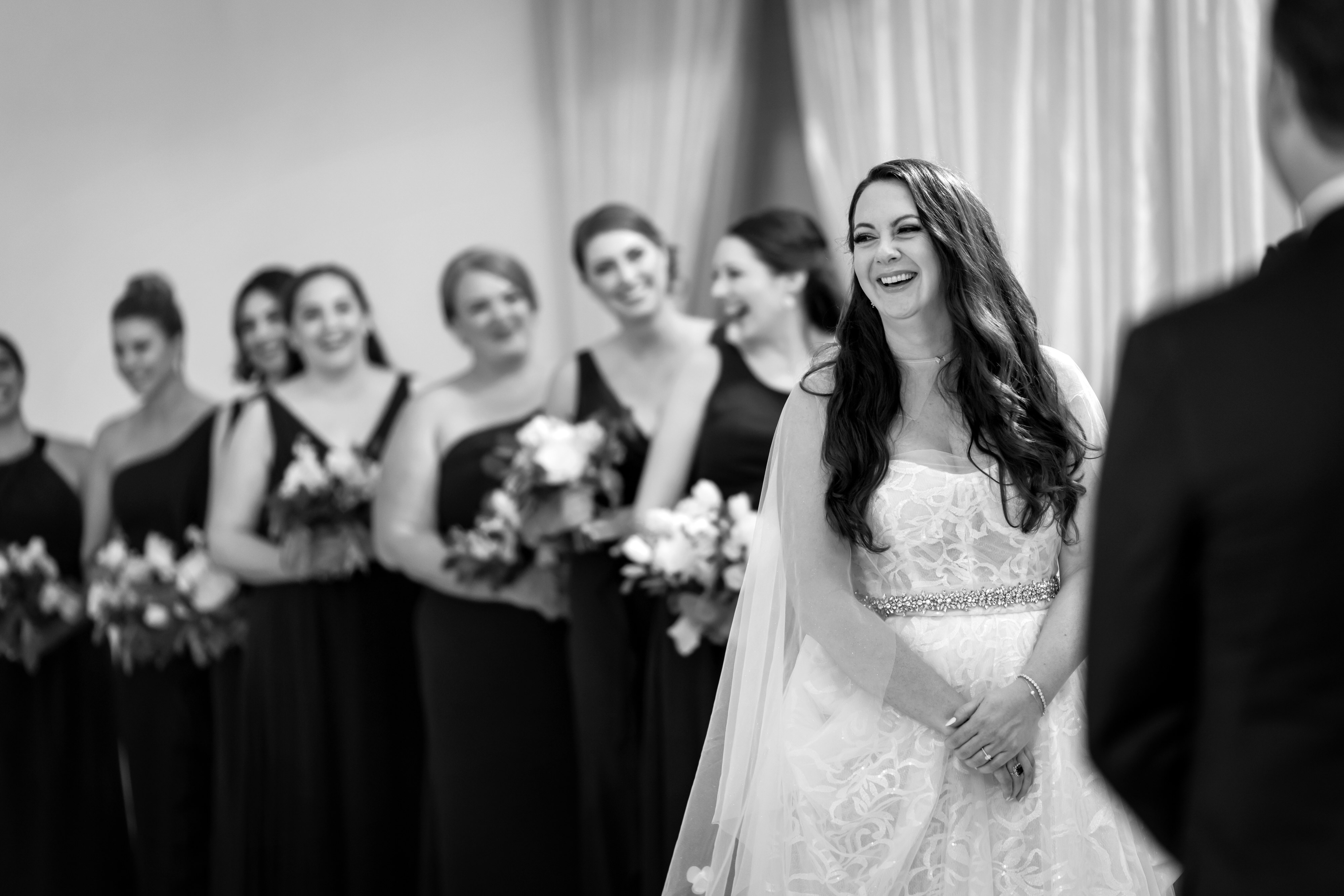 bride and bridesmaids laugh during wedding ceremony at Stan Mansion