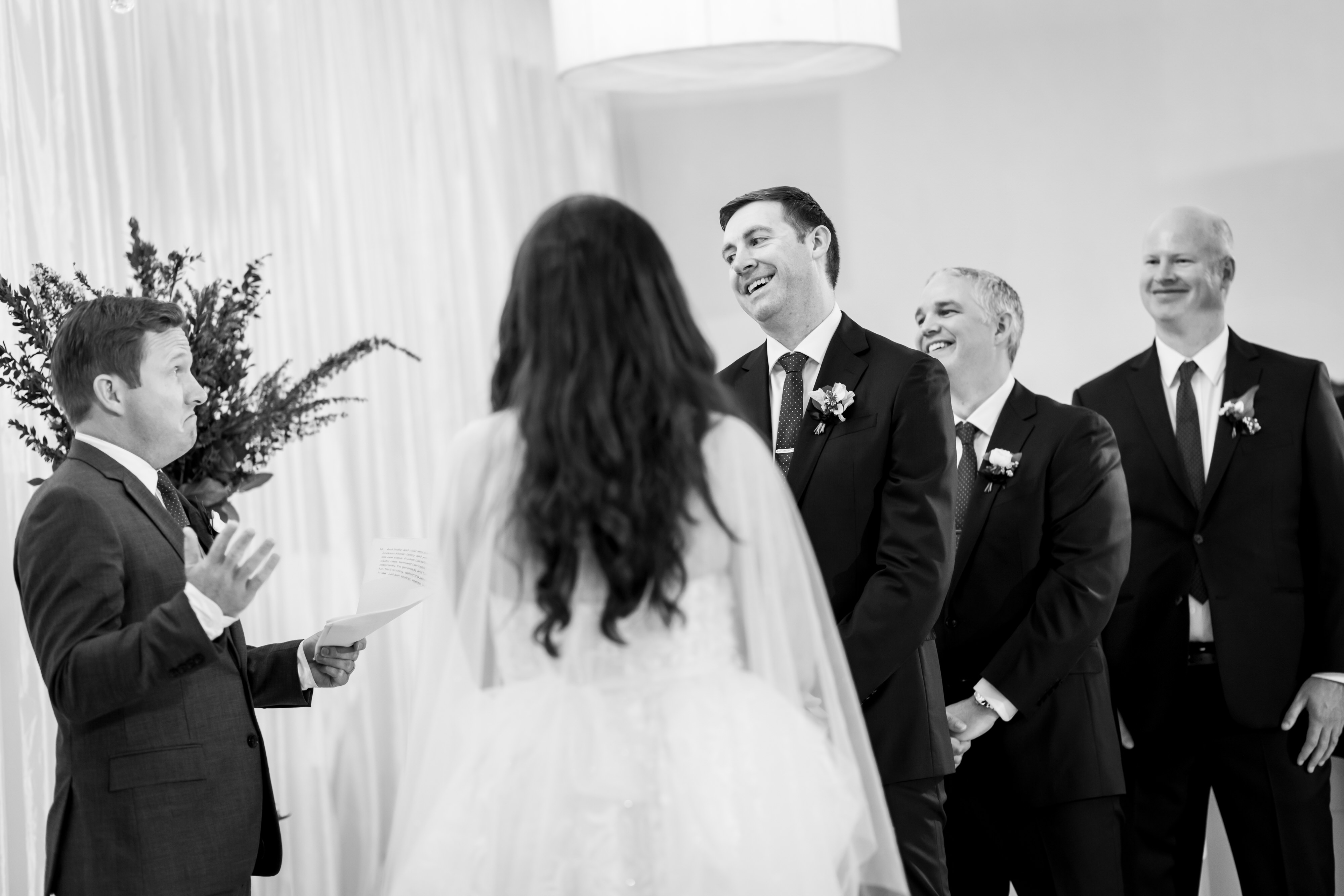 groom and groomsmen laugh during wedding ceremony at Stan Mansion