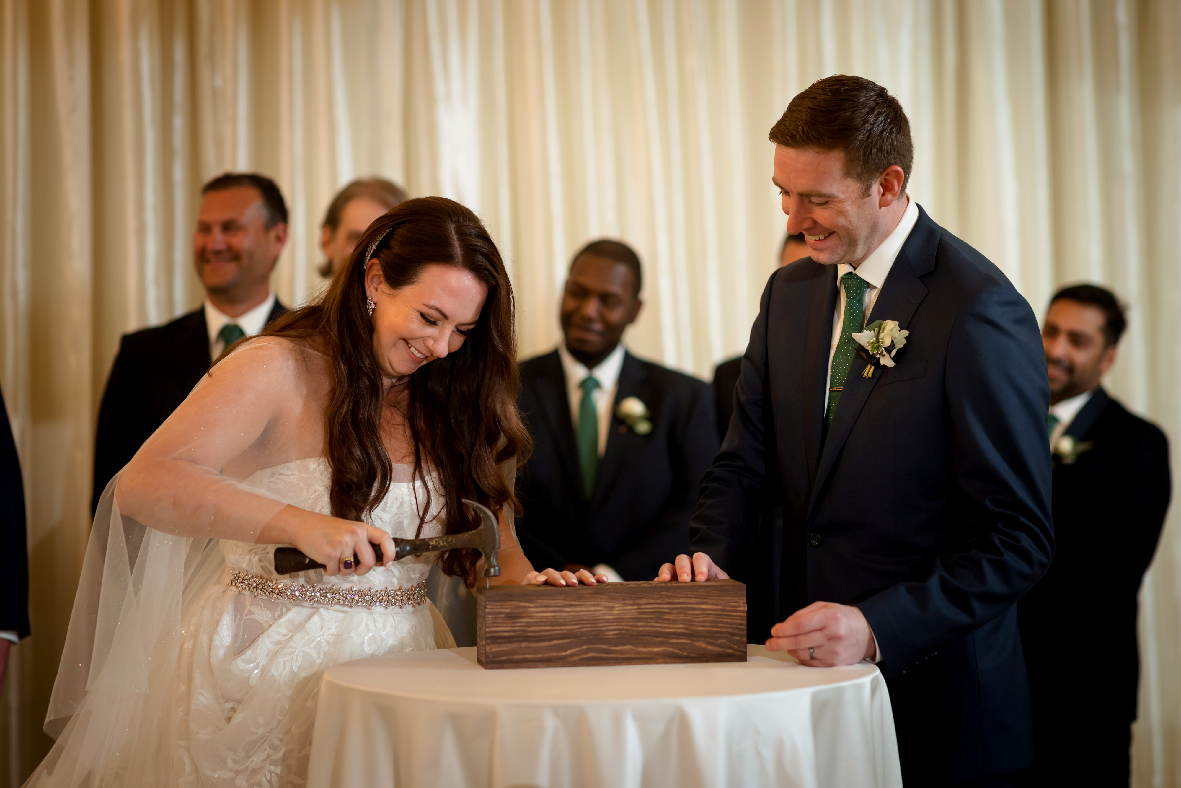 bride pounds nail into wood box of wine with groom at their wedding ceremony