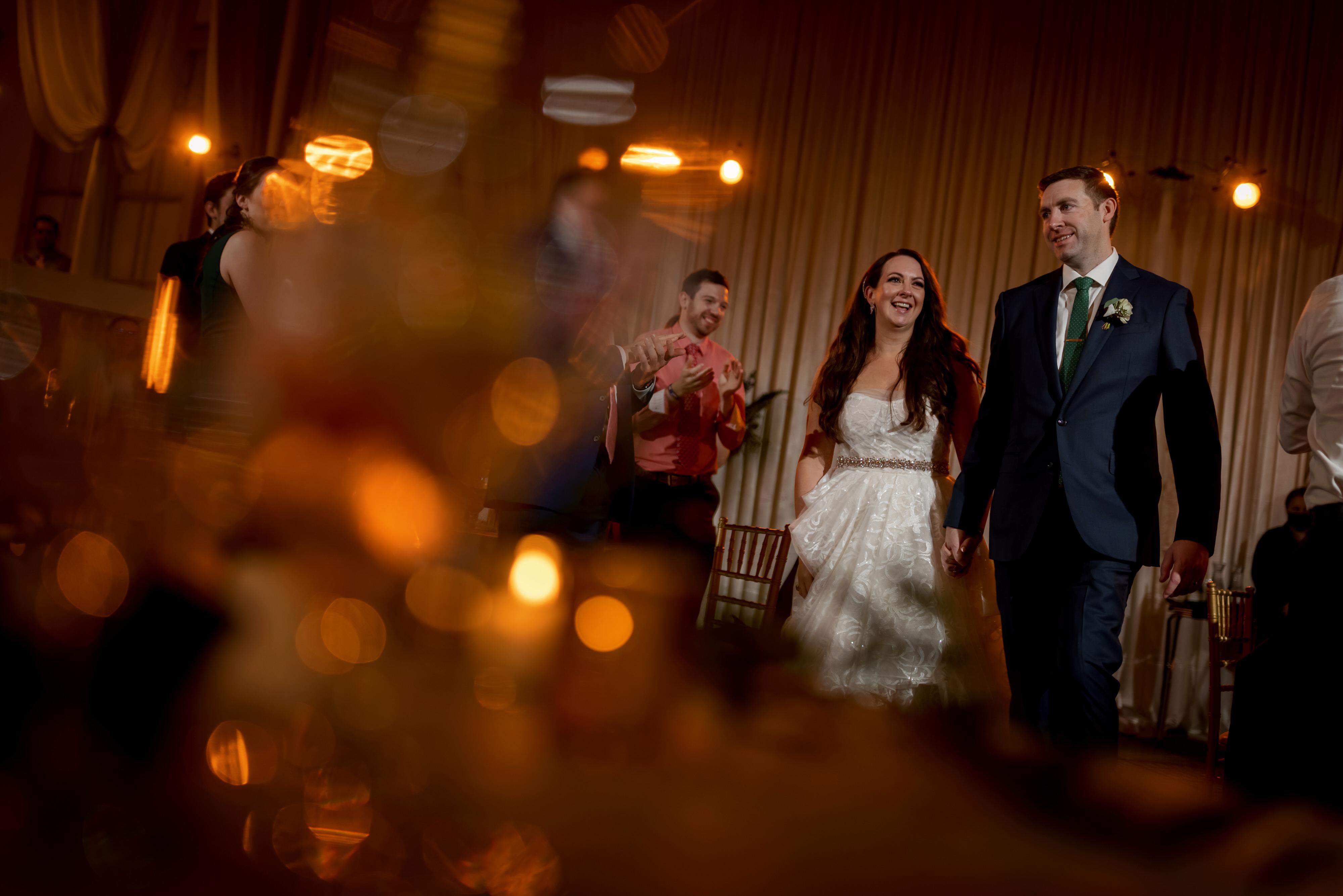 bride and groom walk into wedding reception at Stan Mansion