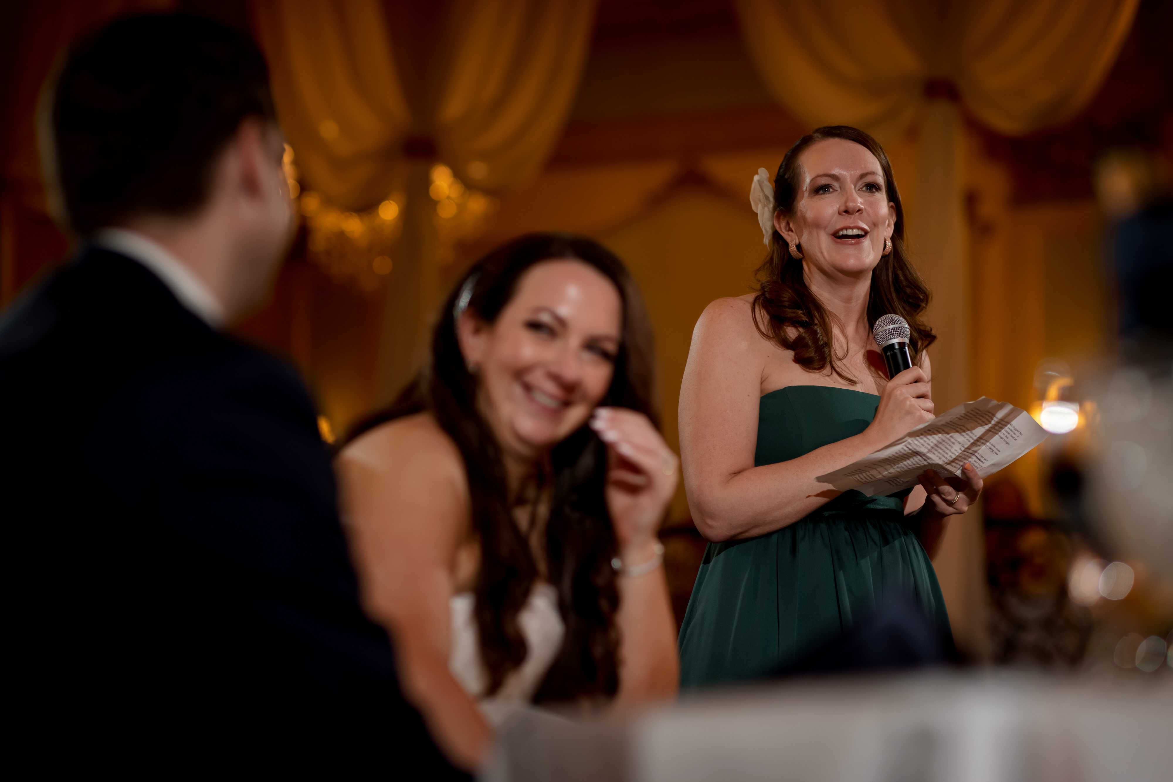 bride and groom react during toast by maid of honor during wedding reception at Stan Mansion