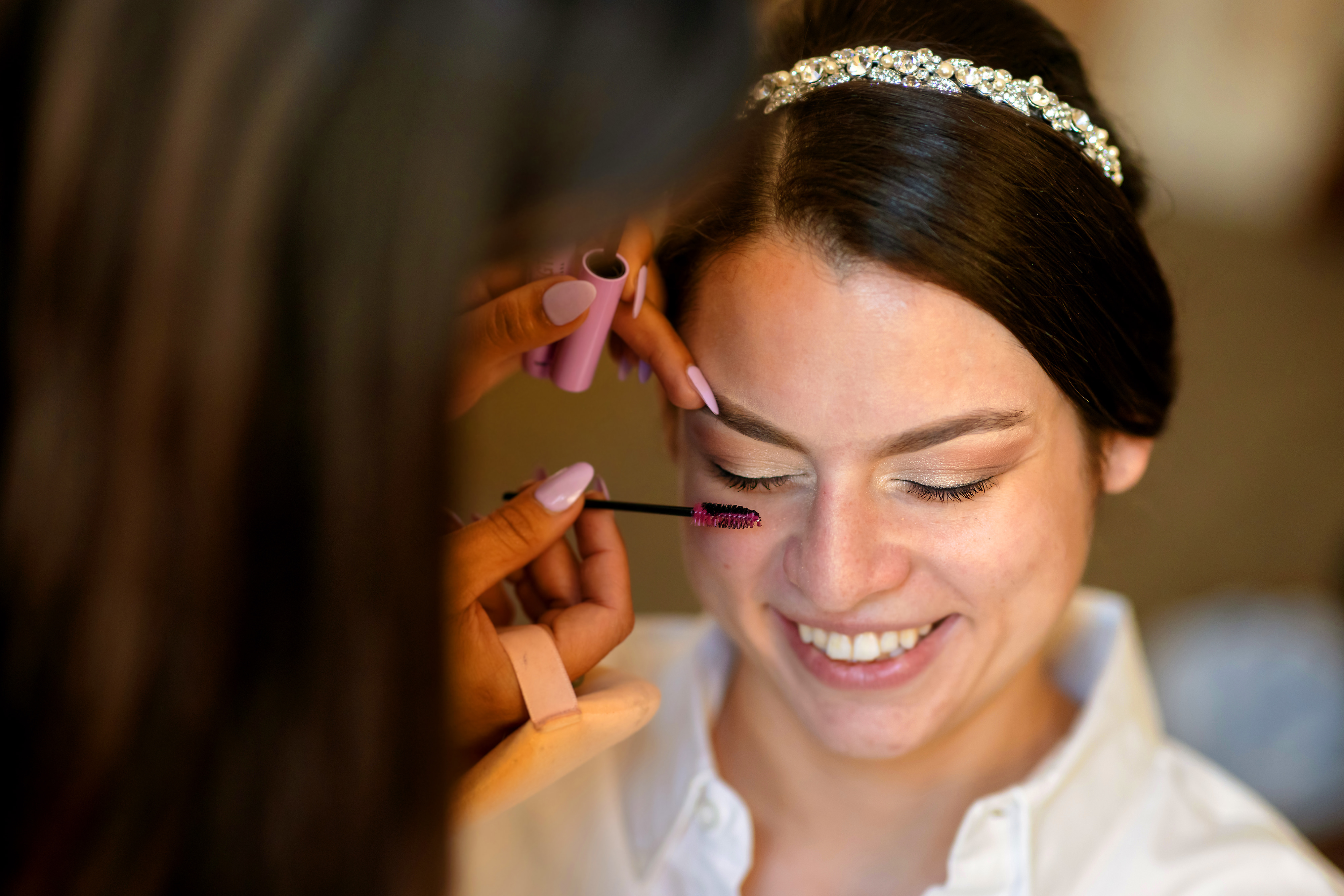 Bride has her makeup done while getting ready for a wedding