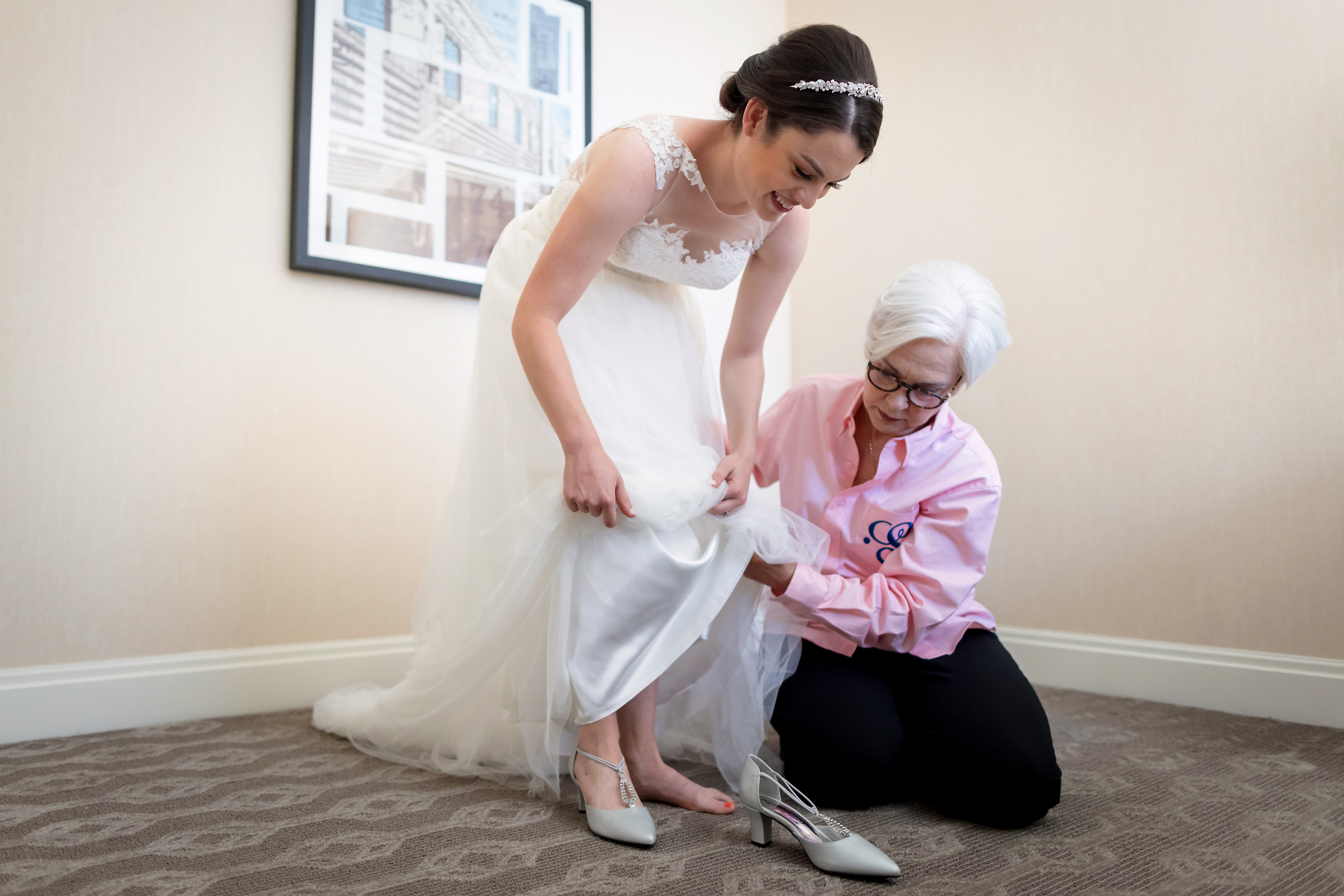 Mom helps bride put on shoes while getting ready for her wedding