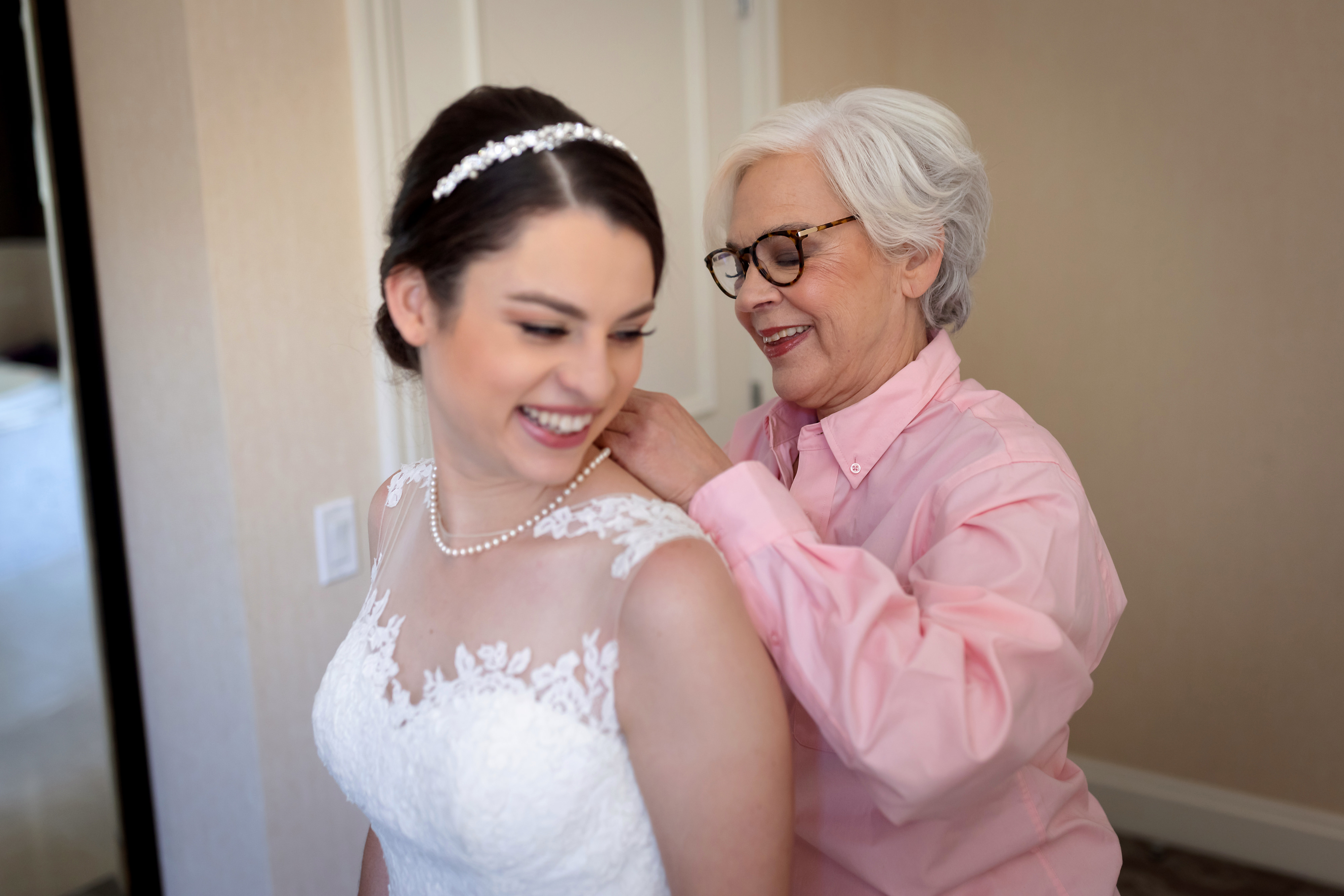 Mom helps bride put on necklace while getting ready for wedding