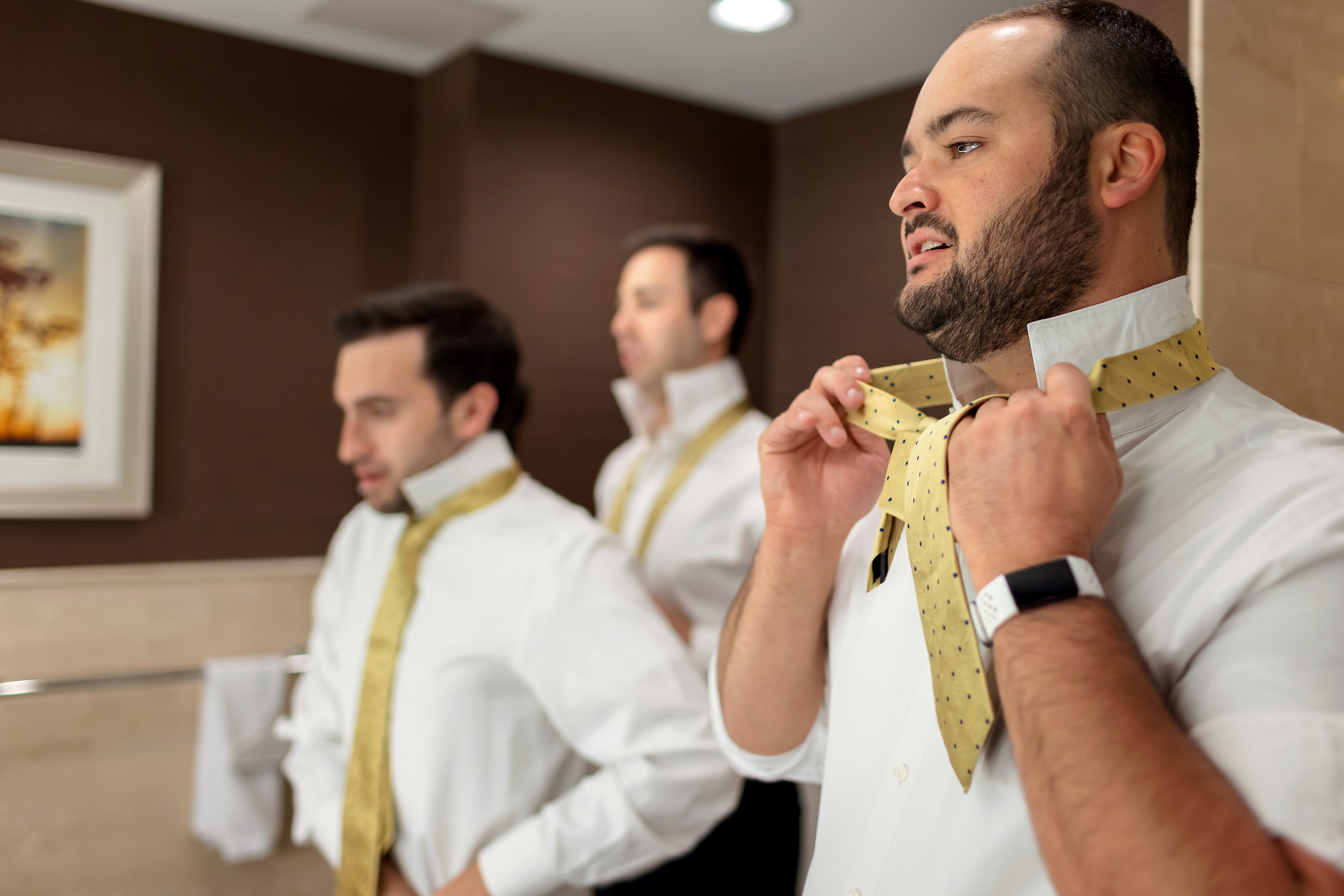 Groomsmen put on ties while getting ready for wedding