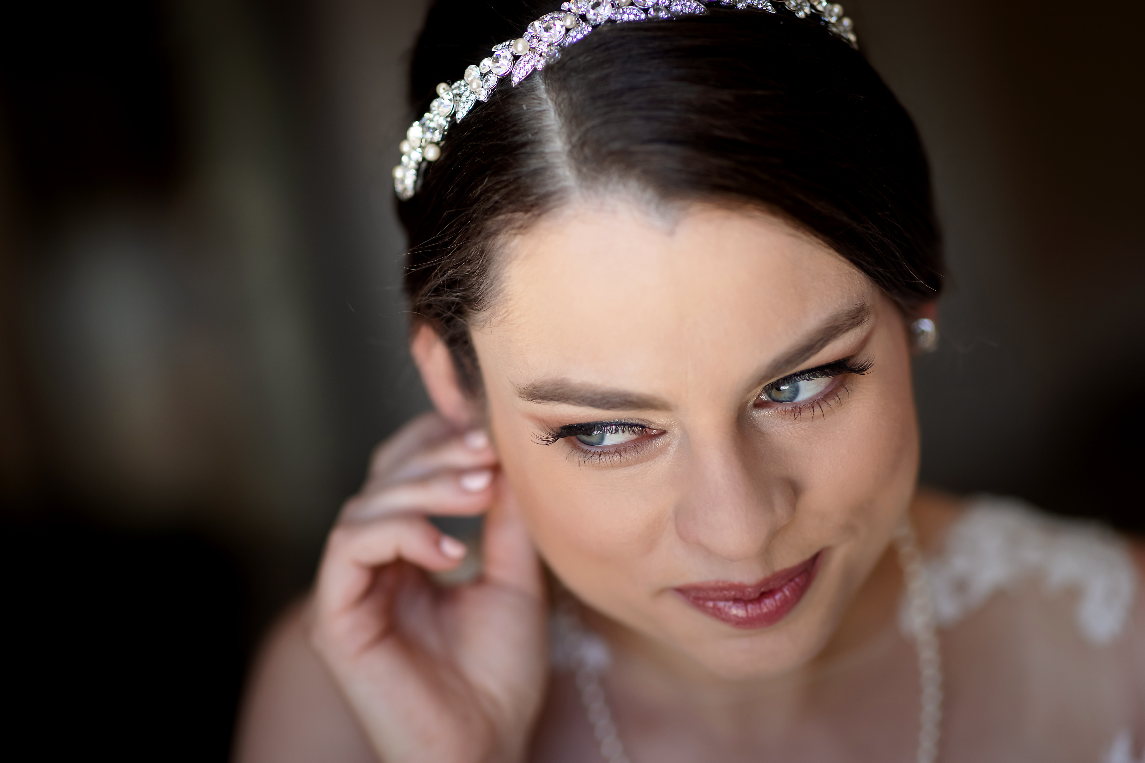 Bride smiles while putting on earring