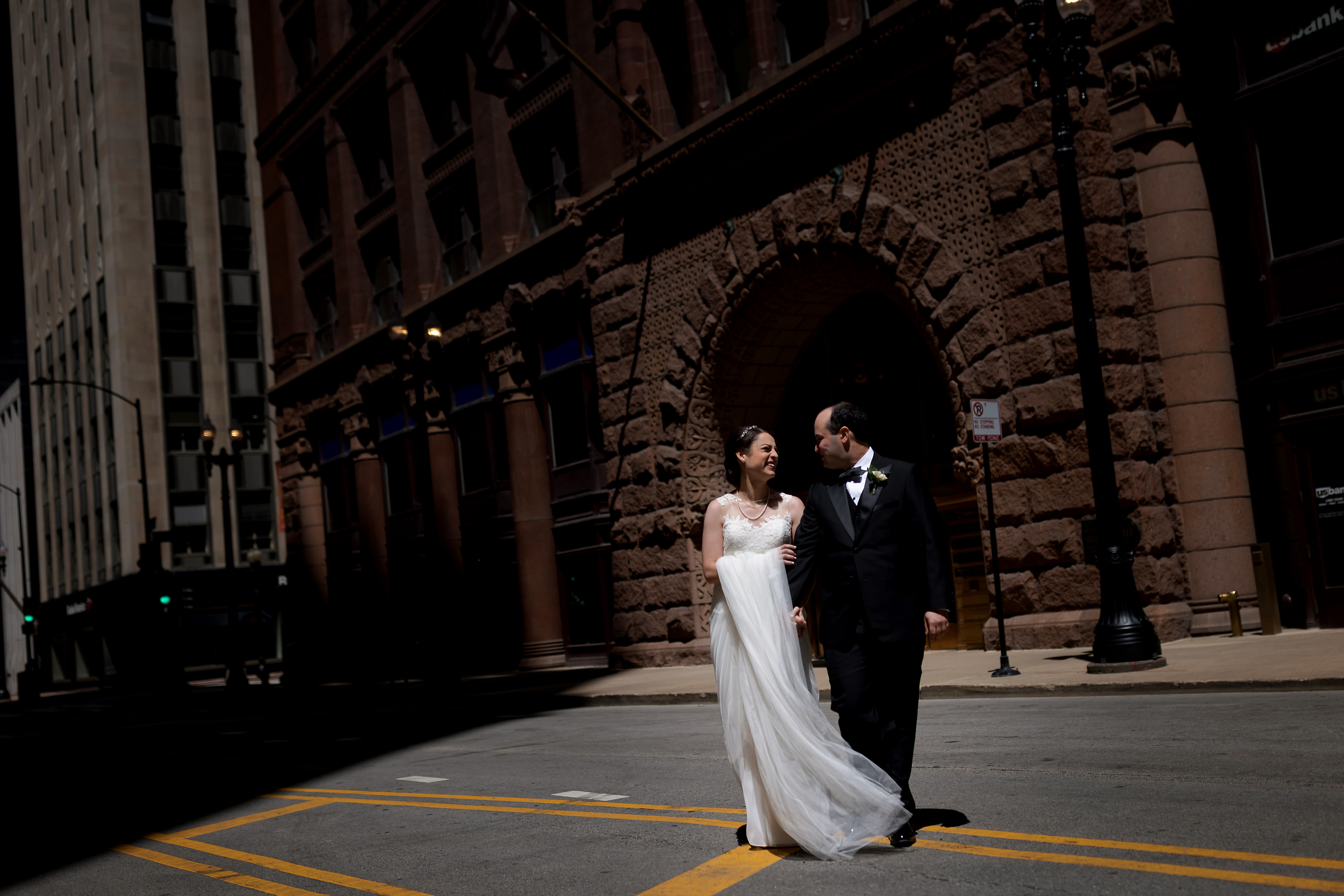 Bride and groom walk across LaSalle Street outside of the Rookery Building in Chicago