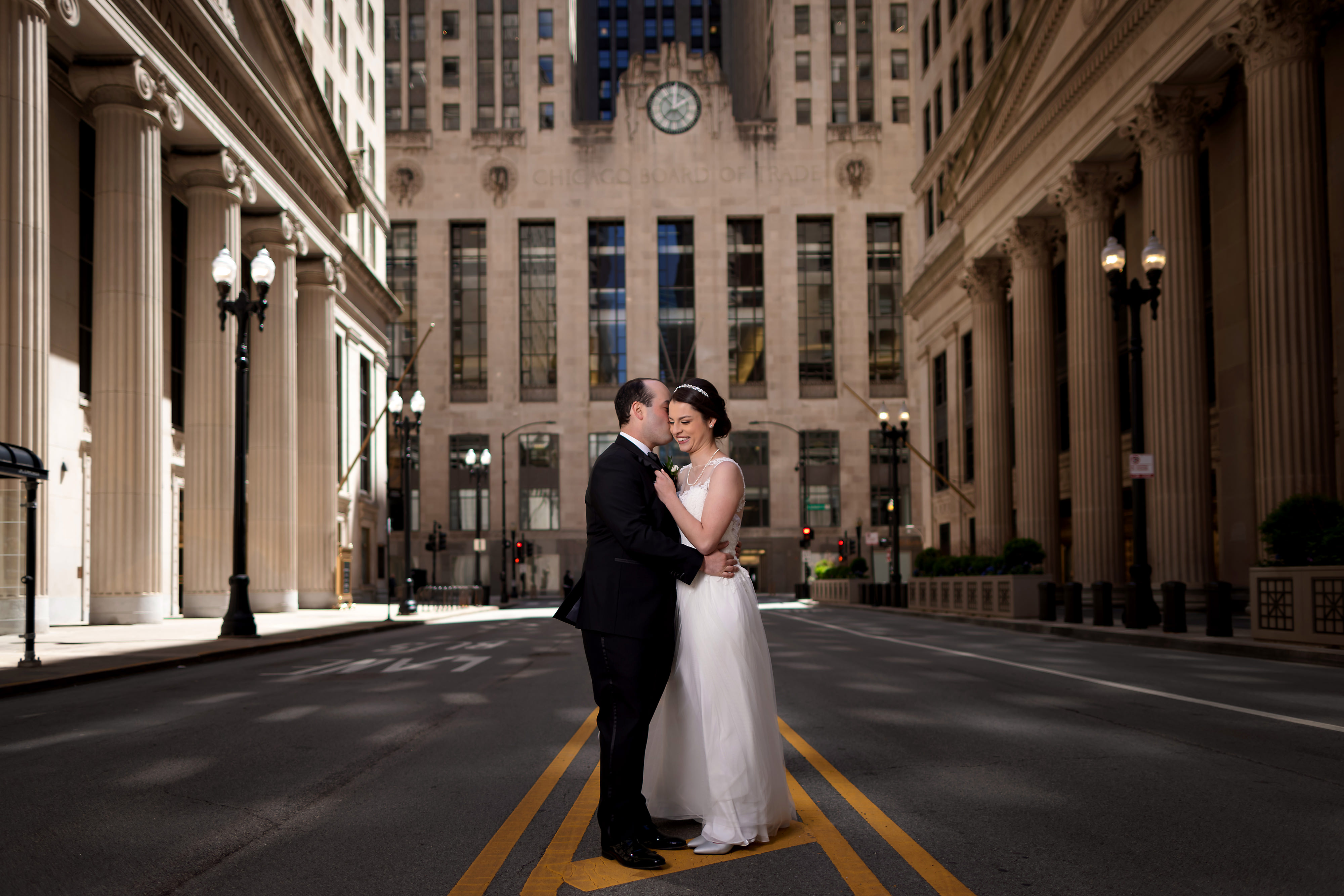 Bride and Groom pose for portrait in front of the Board of Trade building on LaSalle Street in downtown Chicago