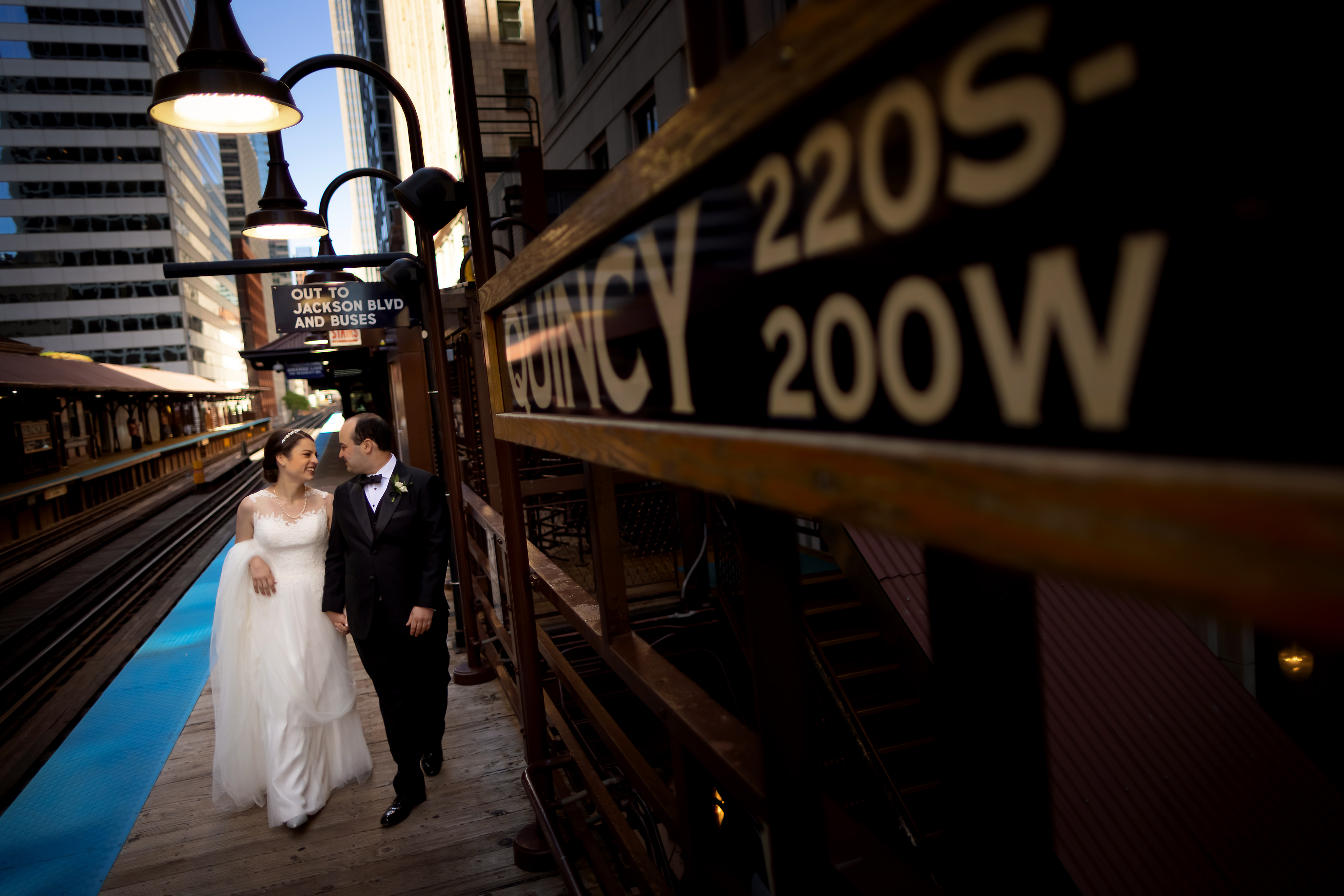 Bride and groom pose for wedding portraits at the Quincy Station El stop in Chicago