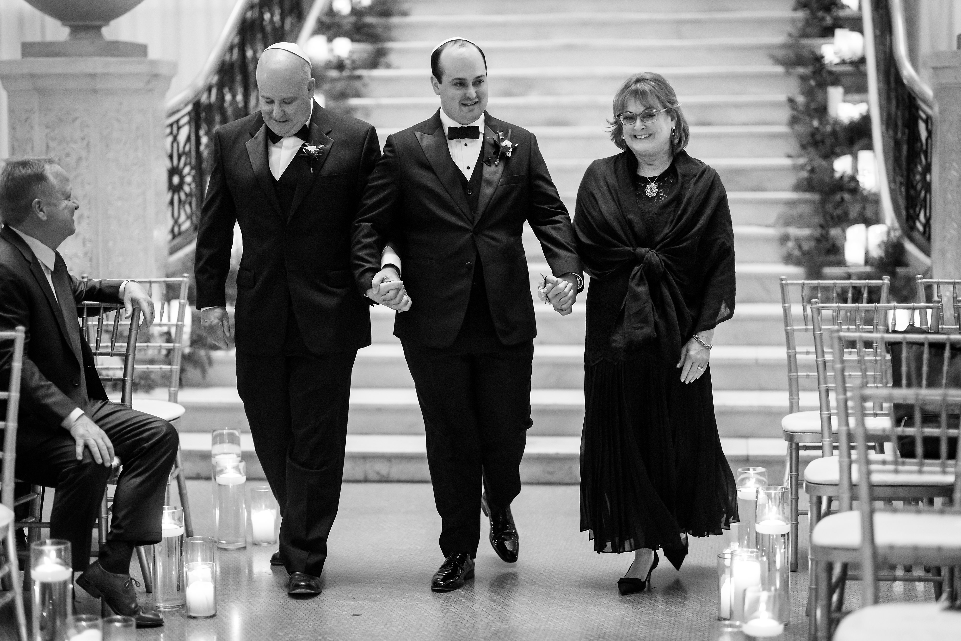 Groom walks in with parents during wedding ceremony at the Rookery Building in Chicago