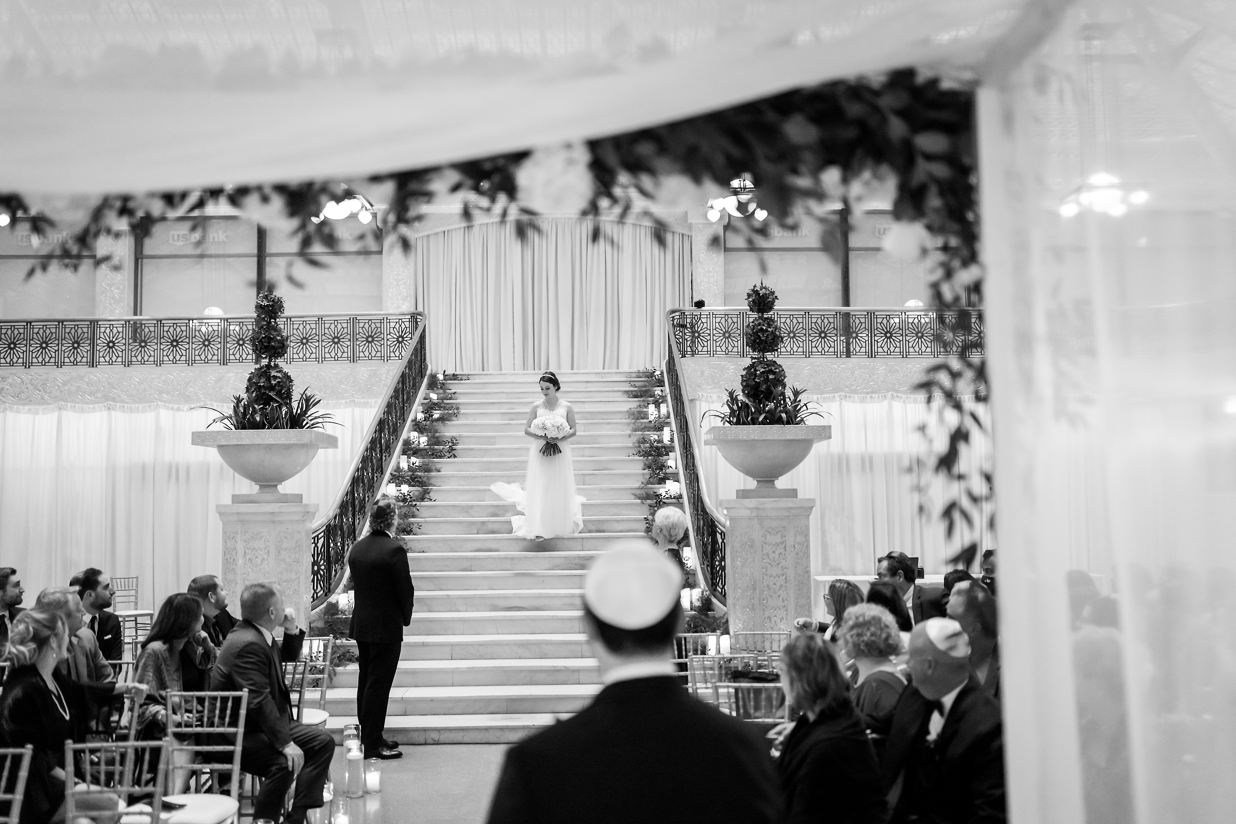 Bride walks in with parents during wedding ceremony at the Rookery Building in Chicago