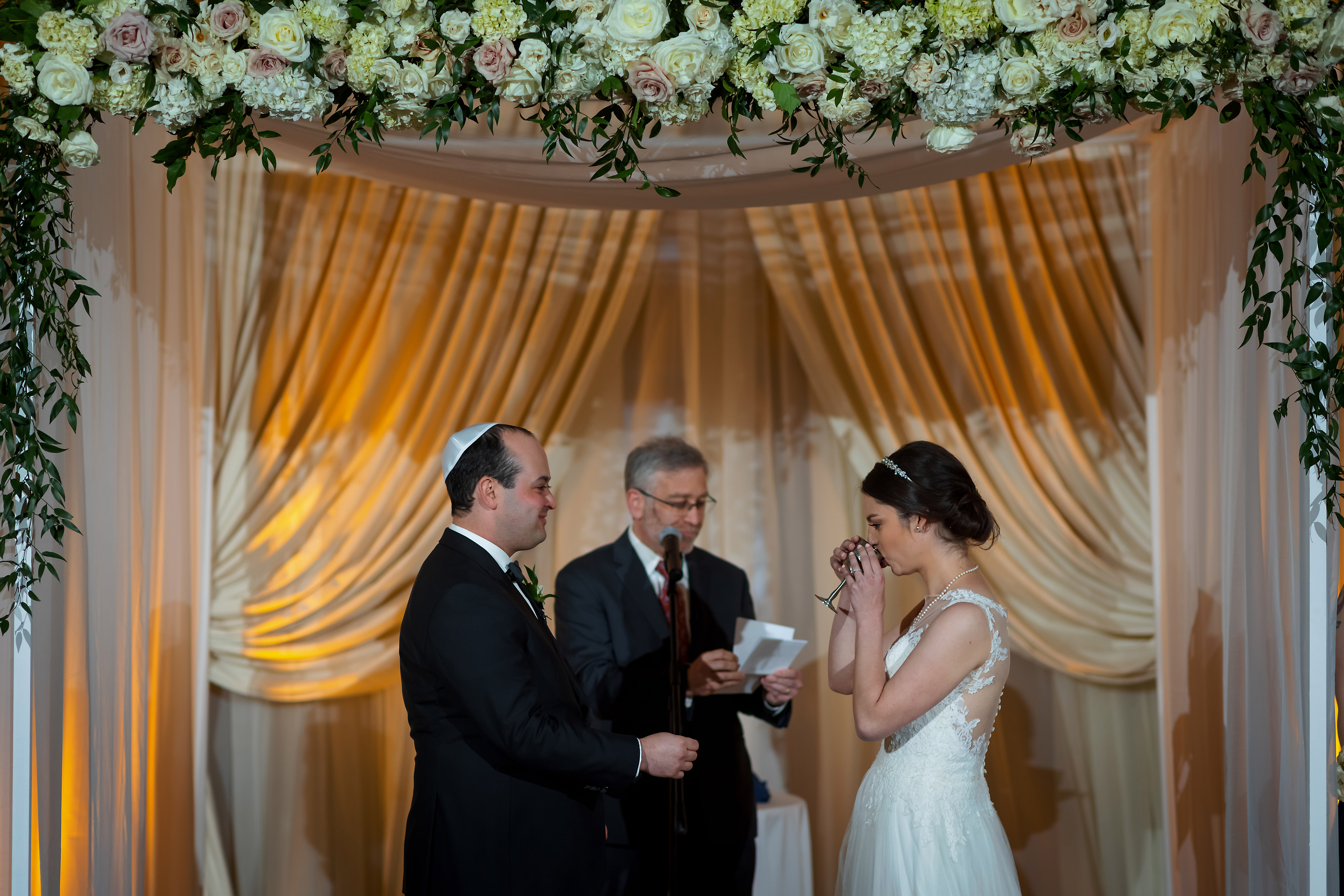 Bride sips from a cup of wine during wedding ceremony at the Rookery Building in Chicago