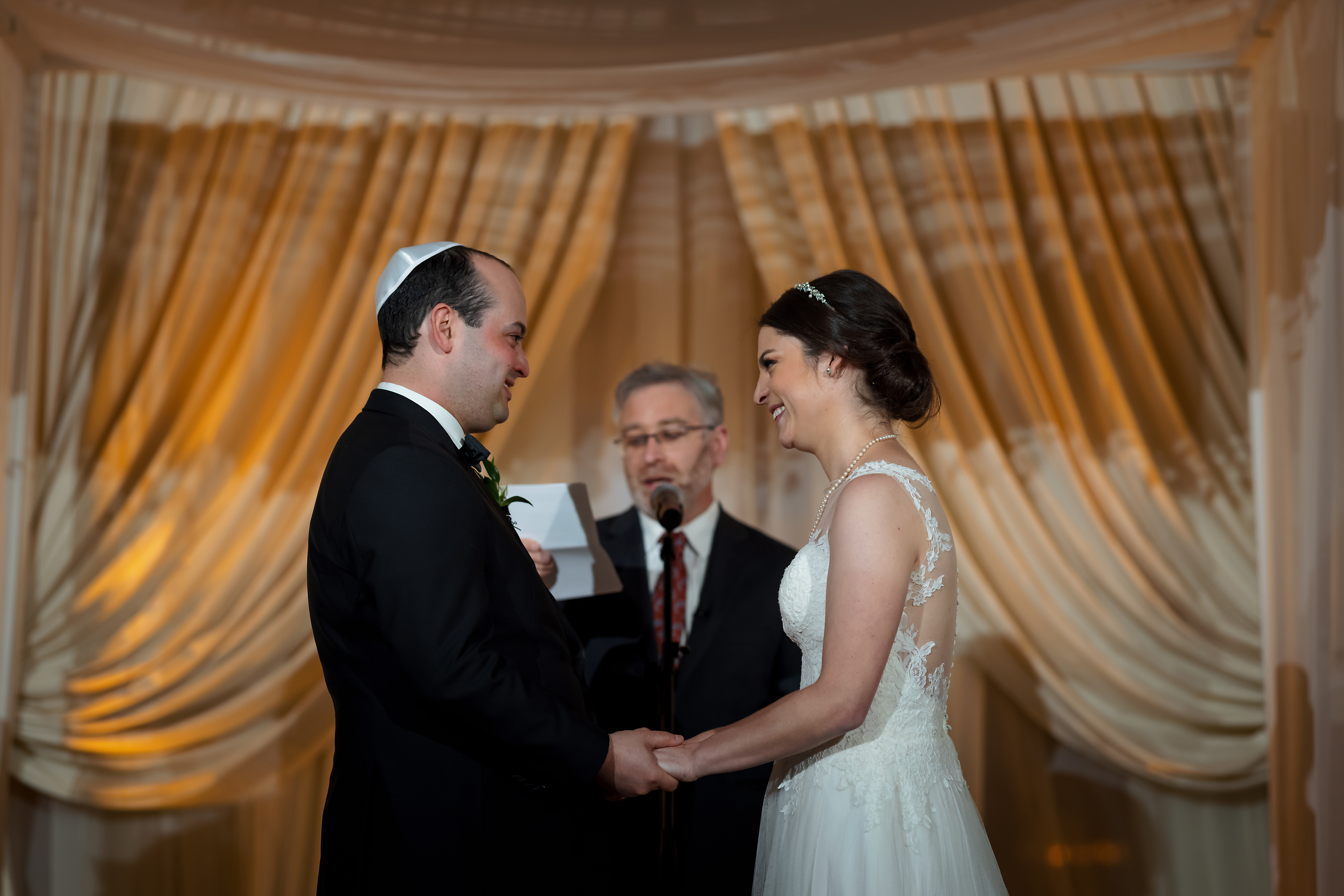 Bride and groom hold hands during wedding ceremony at the Rookery Building in Chicago