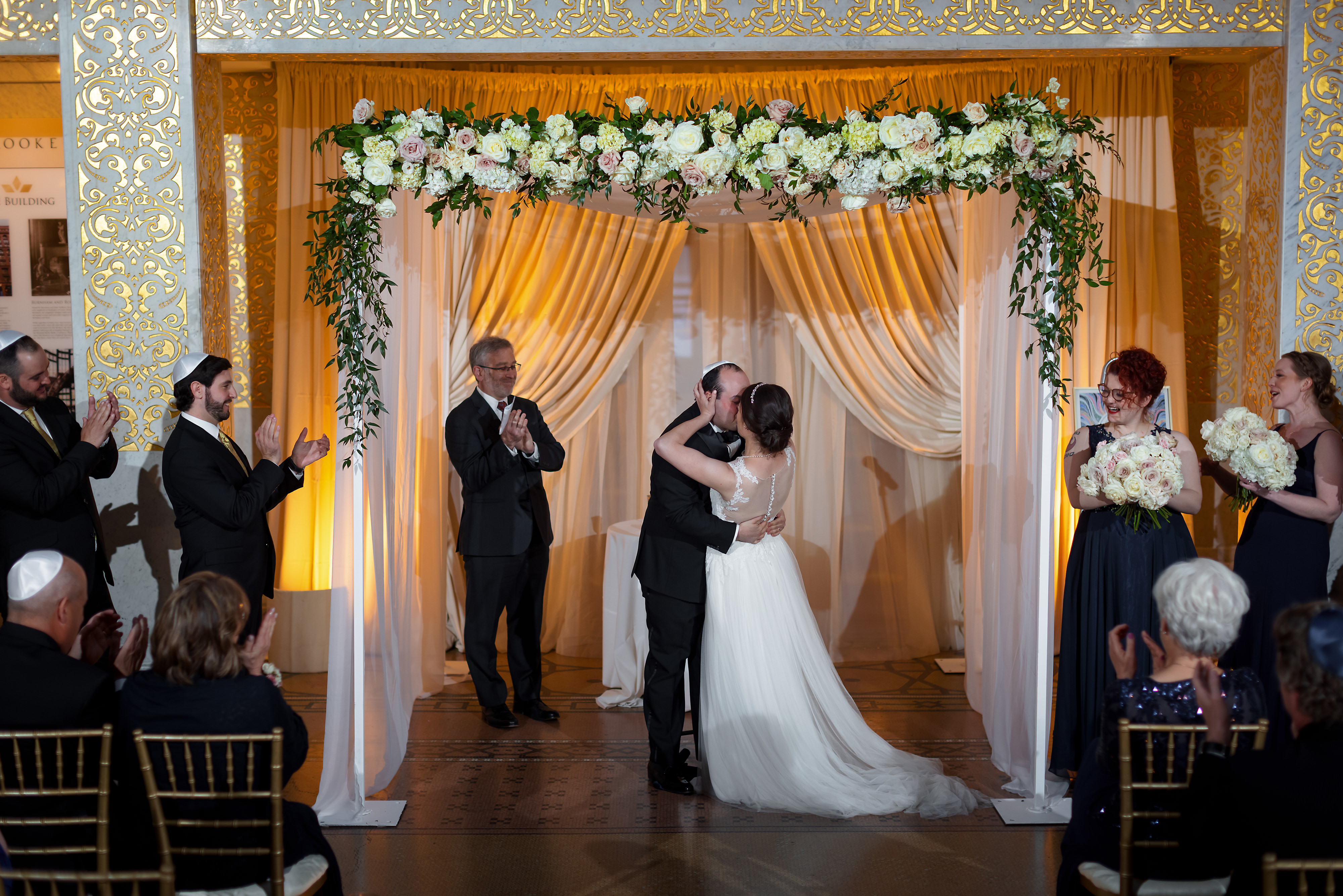 Bride and groom kiss during wedding ceremony at the Rookery Building in Chicago