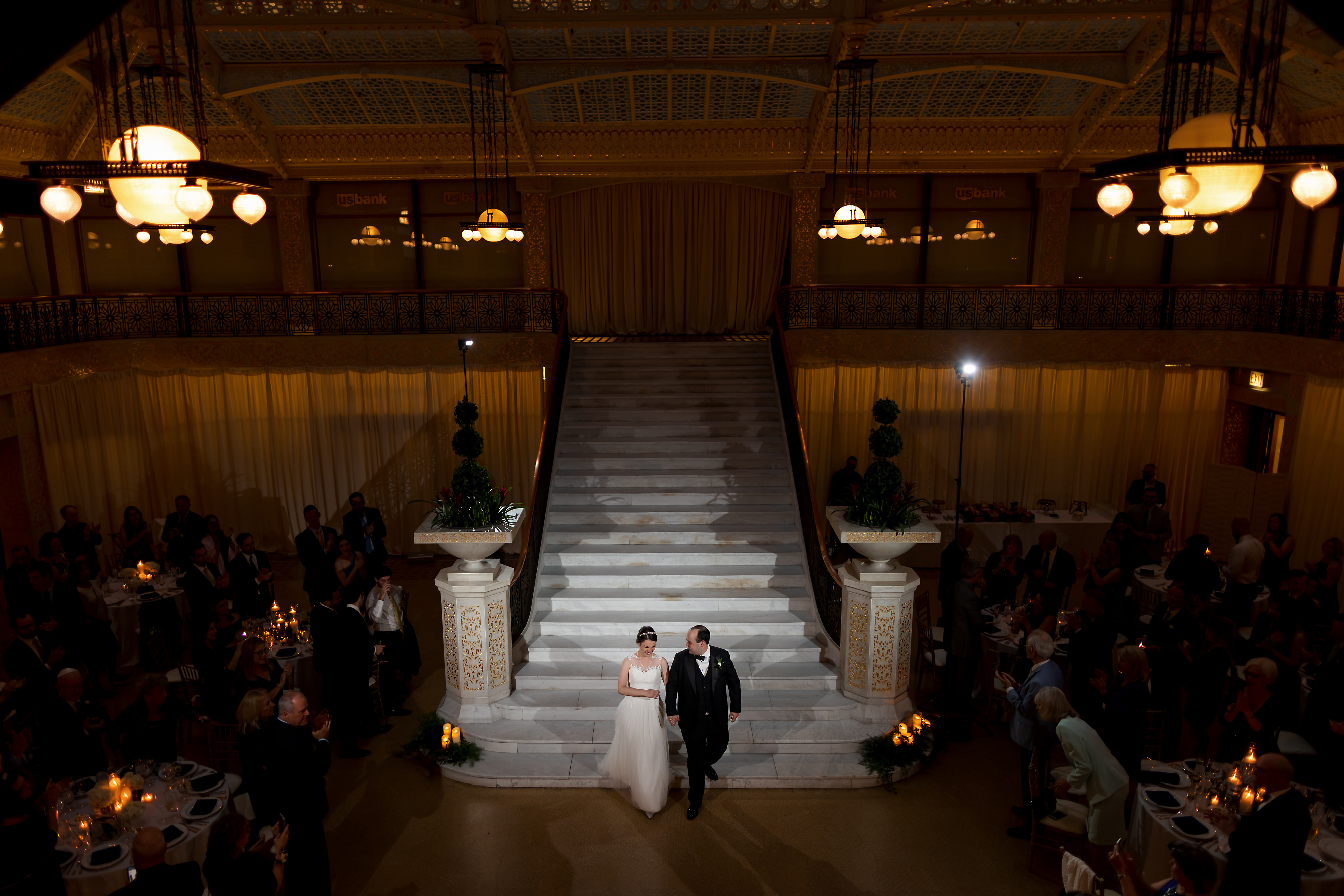 Bride and Groom walk down staircase into wedding reception at the Rookery Building in Chicago