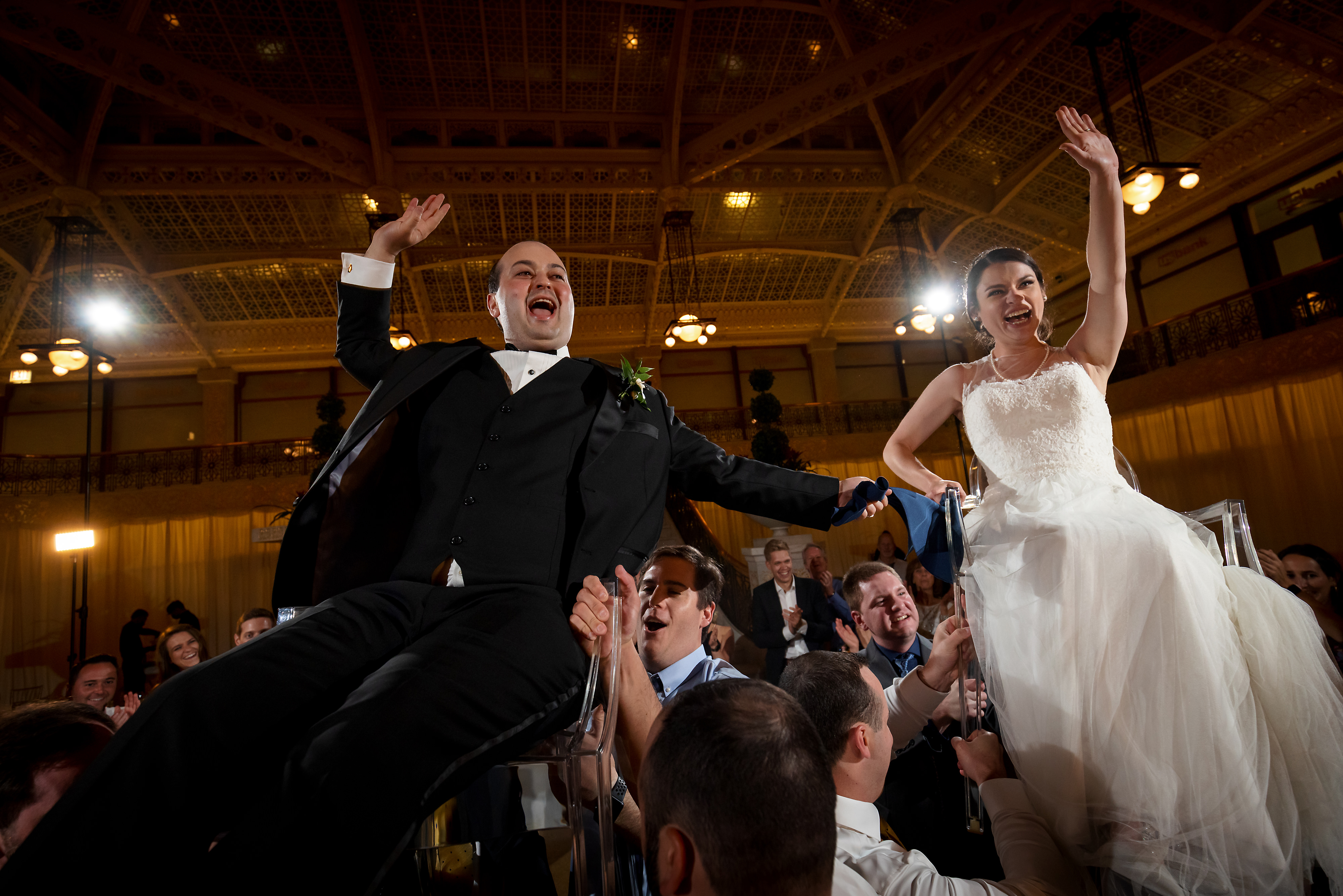 Bride and groom are lifted in chairs by guests during Hora dance of wedding reception at the Rookery Building in Chicago