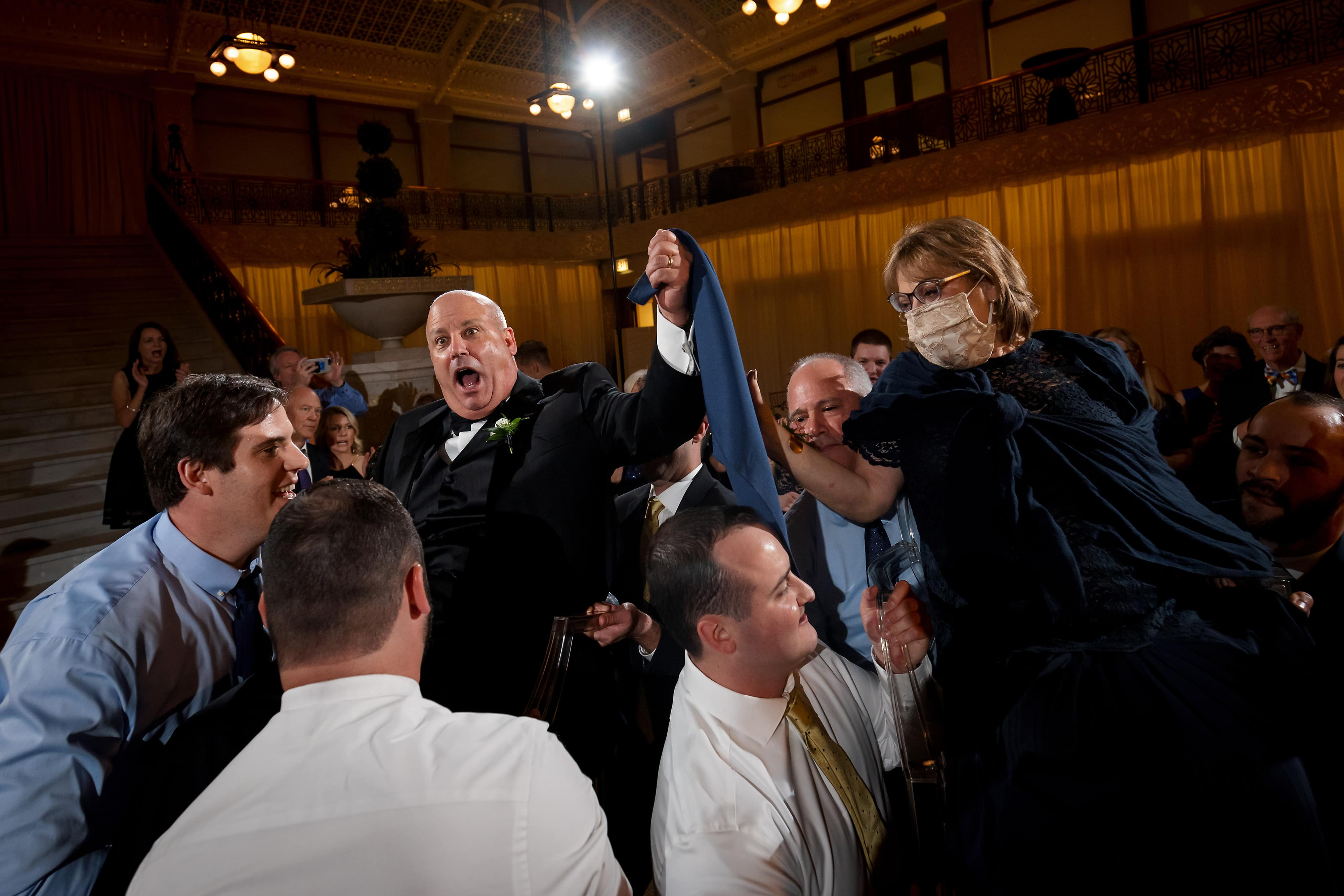 Parents of the groom are lifted in chairs by guests during Hora dance of wedding reception at the Rookery Building in Chicago