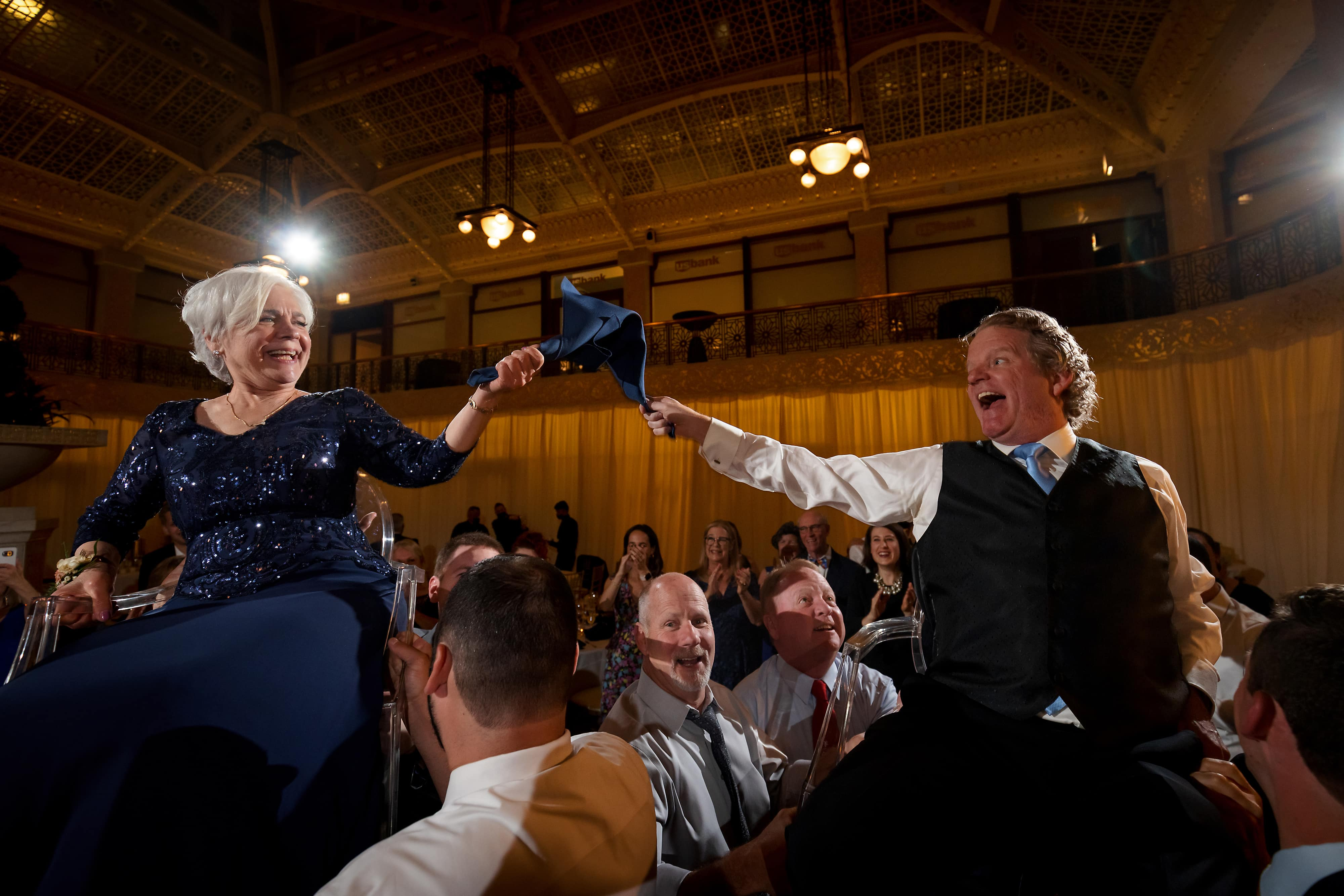 Parents of the bride are lifted in chairs by guests during Hora dance of wedding reception at the Rookery Building in Chicago