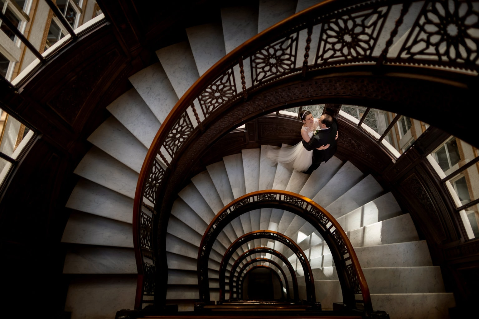 Bride and groom pose for portrait on the historic spiral staircase at the Rookery Building in downtown Chicago