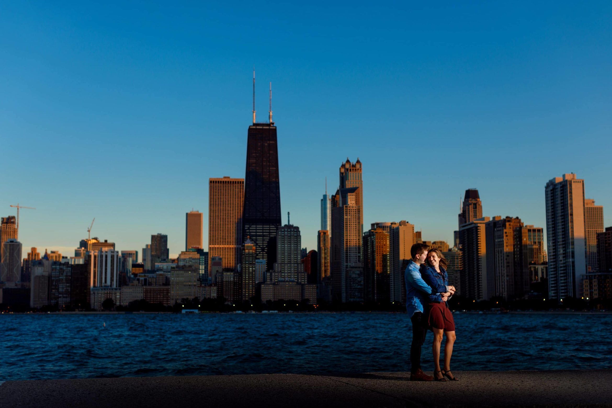 Off-camera-flash-lit-photo-of-a-couple-posing-for-engagement-photos-at-North-Ave.-Beach-during-their-Chicago-engagement-session-with-skyline-in-the-background-05