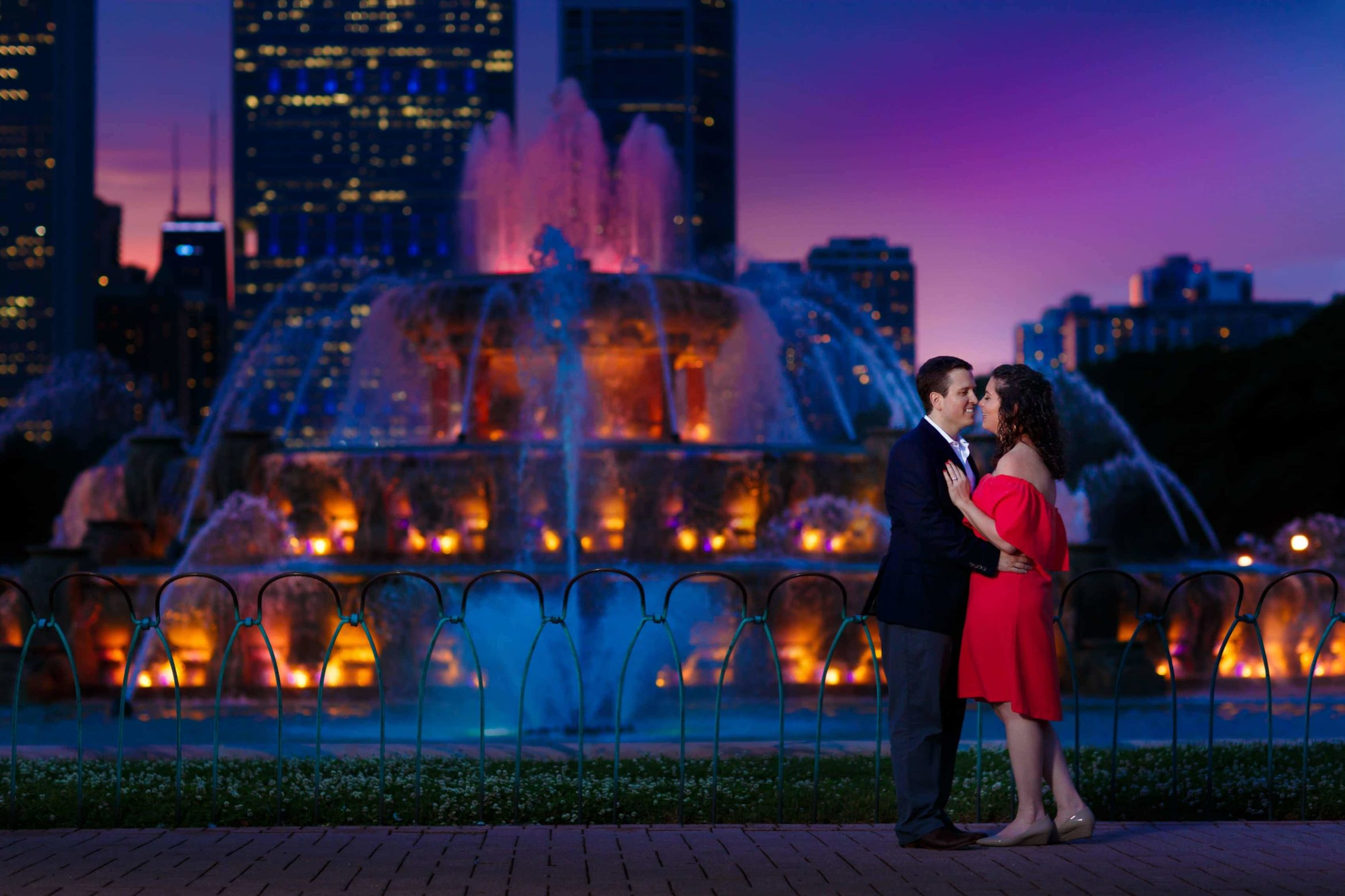 a-couple-laughs-together-during-their-Buckingham-Fountain-engagement-photos-night-engagement-session-in-downtown-Chicago-05
