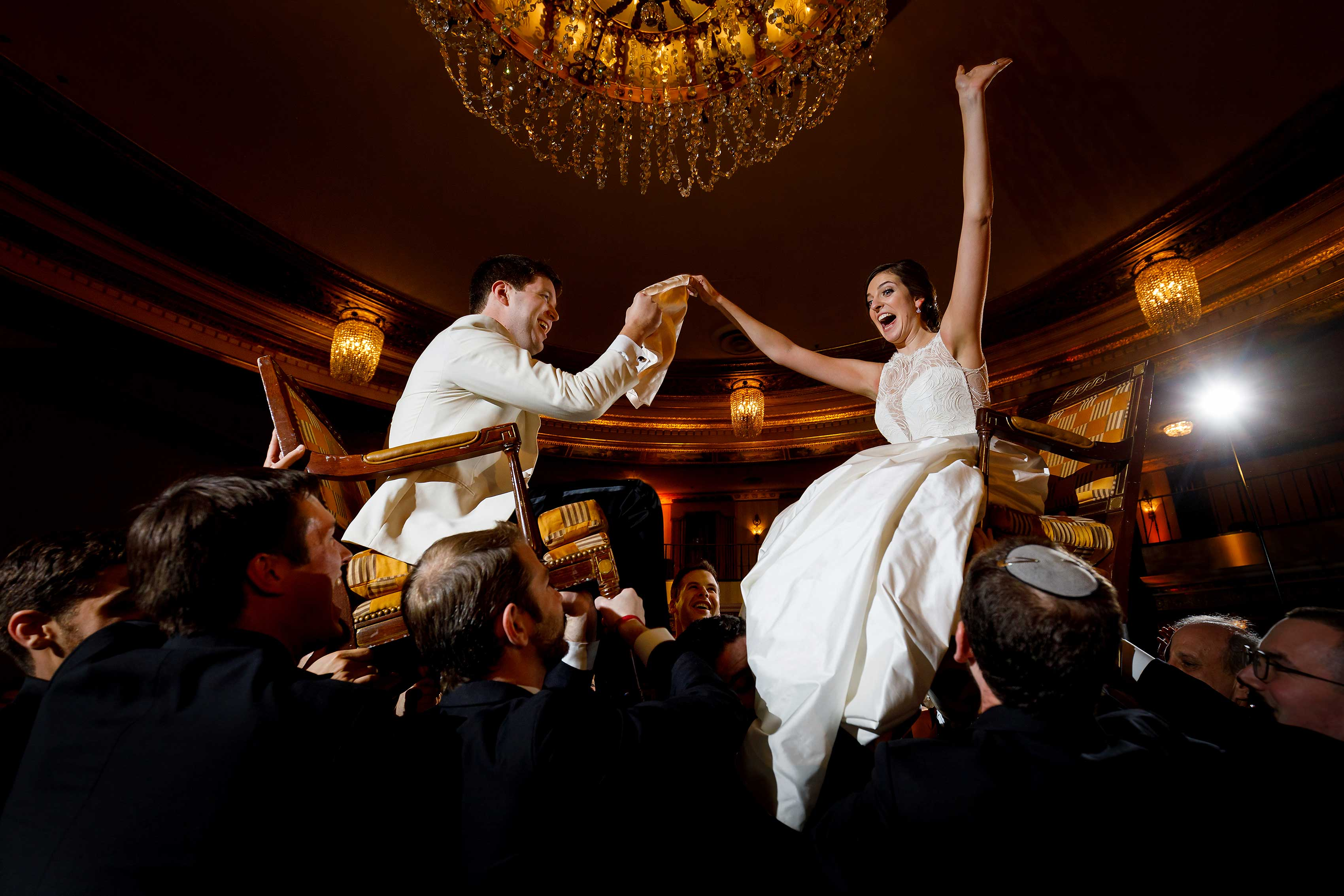 bride-and-groom-are-lifted-onto-chairs-during-the-Horah-during-Jewish-wedding-reception-at-InterContinental-Chicago-Magnificent-Mile-Hotel-31