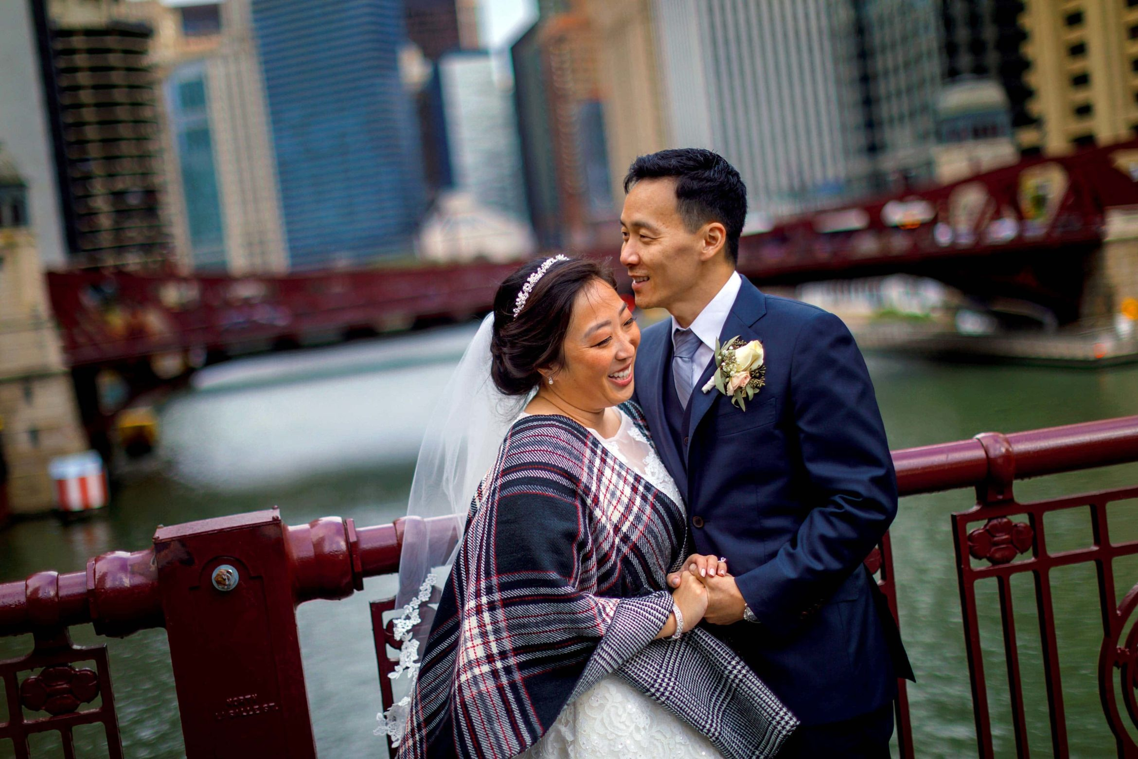 bride-and-groom-laugh-during-portraits-on-LaSalle-Street-Bridge-in-Chicago-following-their-wedding-26