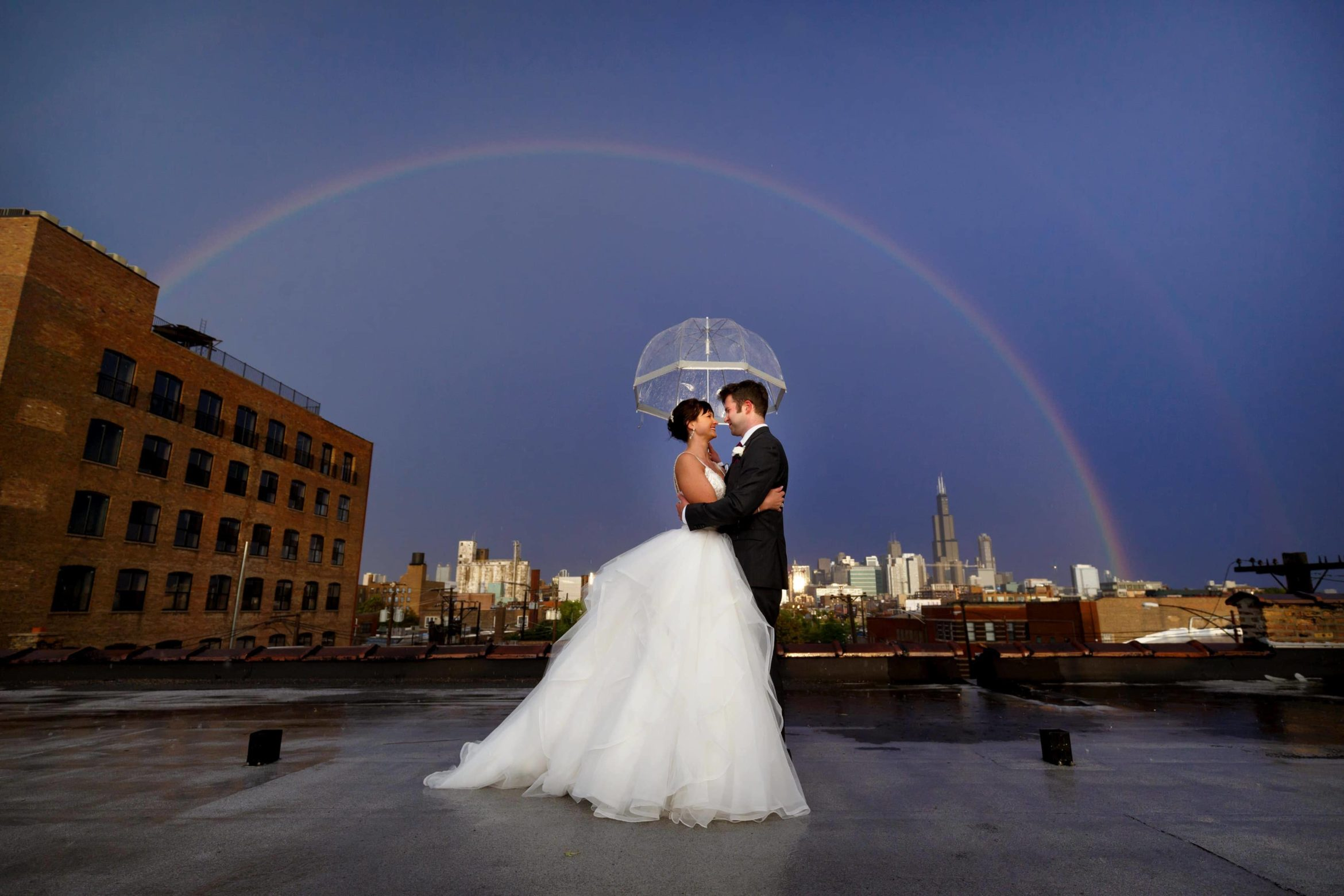 bride-and-groom-pose-for-a-wide-angle-chicago-skyline-rainbow-wedding-photo-under-an-umbrella-on-the-rooftop-of-Room-1520-35