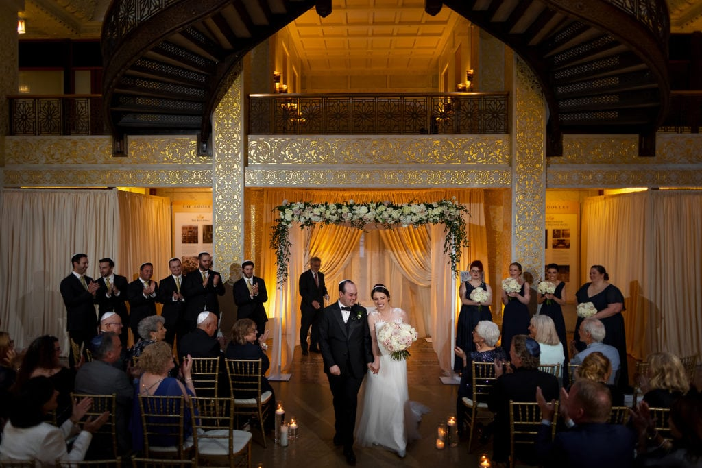 Bride and Groom walk out at the end of wedding ceremony at the Rookery Building in Chicago